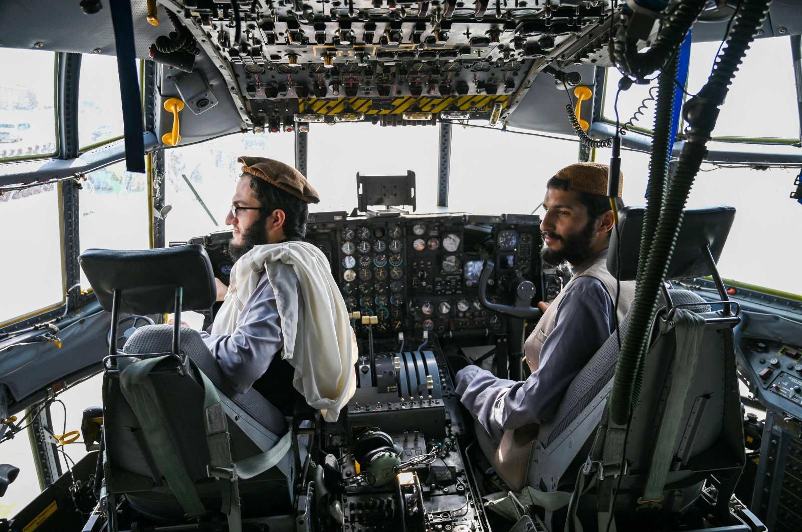 Taliban fighters sit in the cockpit of an Afghan Air Force aircraft at the airport in Kabul, Afghanistan, Aug. 31, 2021. (AFP Photo)