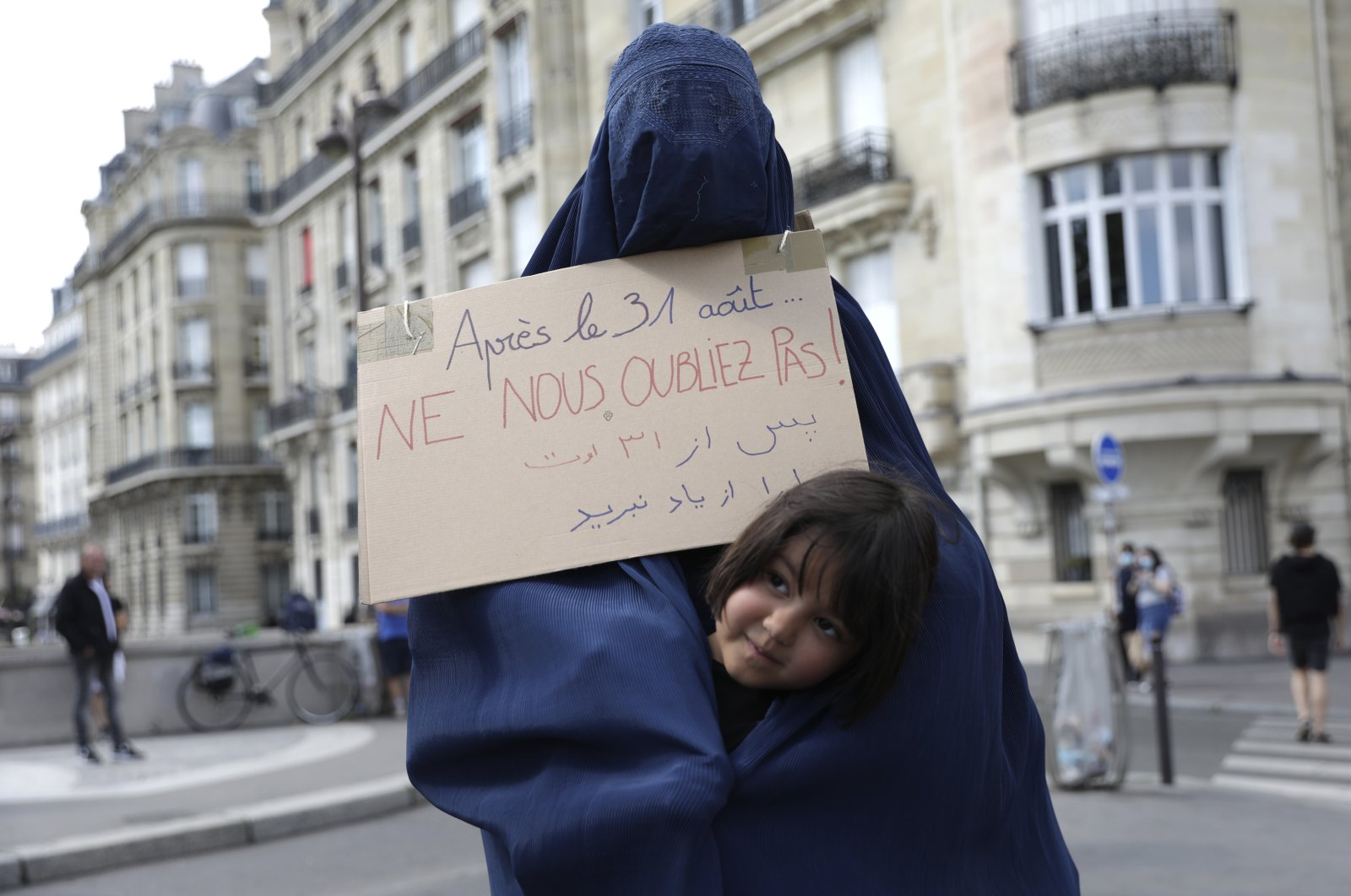 """A woman wearing a burqa and holding a placard reading """"Do not forget us after Aug. 31"""" attends a gathering in a show of solidarity with women from Afghanistan, Paris, France, Aug. 28, 2021. (AP Photo)"""