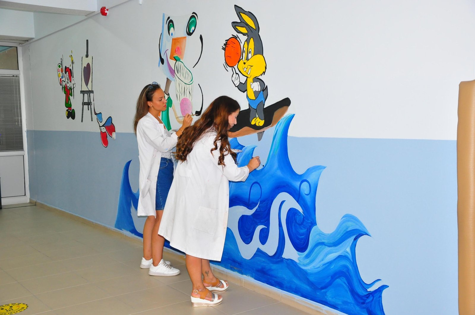 Two teachers paint cartoon characters on the walls of a classroom for preschoolers, in Manisa, western Turkey, Aug. 27, 2021. (DHA PHOTO)