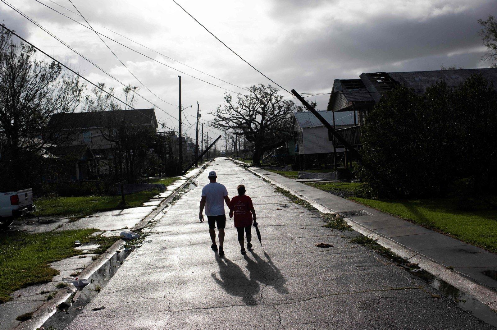 A couple walks down the street while holding hands after Hurricane Ida made landfall, Montegut, Louisiana, U.S., Aug. 30, 2021. (AFP Photo)