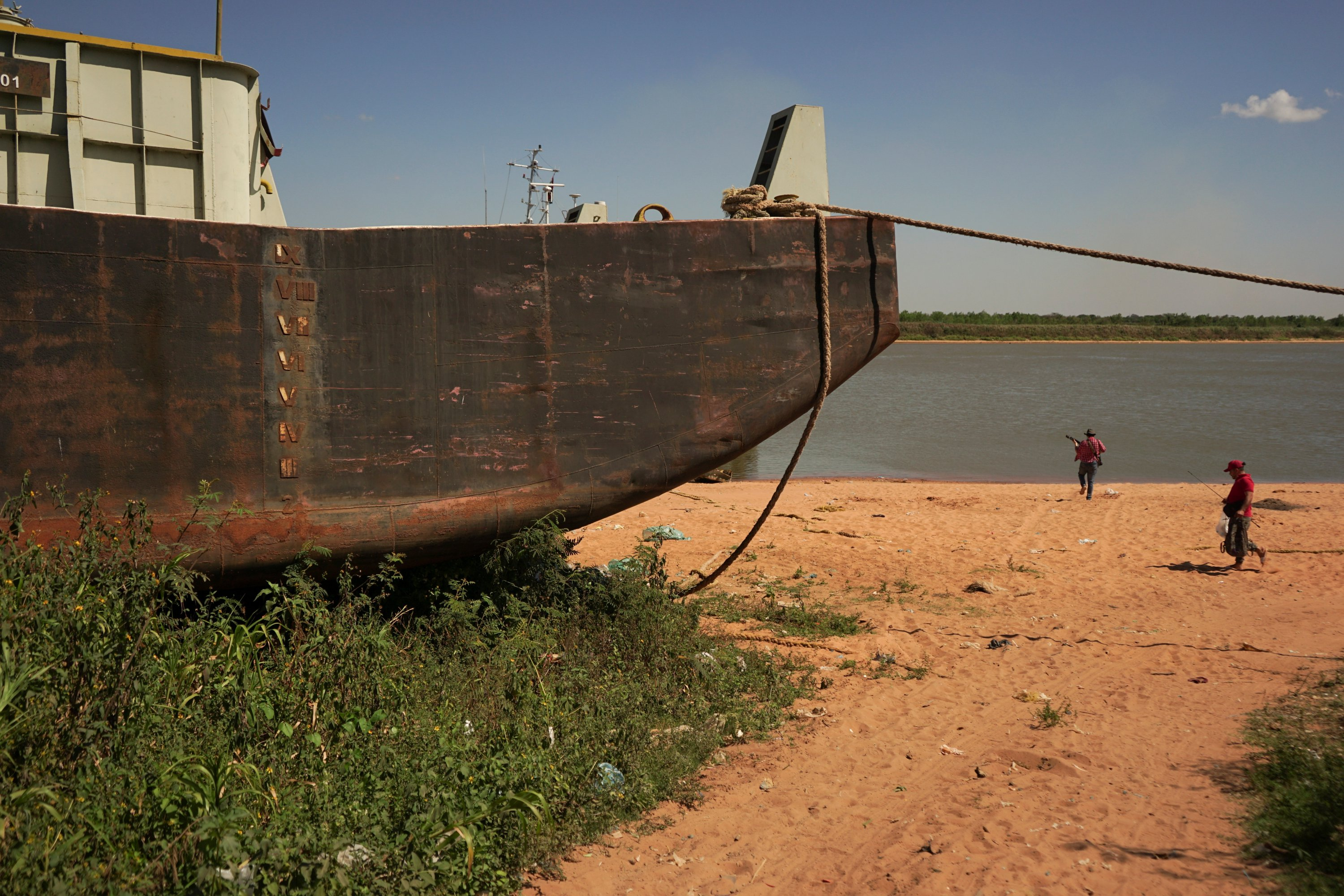 People walk past a stranded barge on the shore of the Rio Paraguay (Paraguay River), which flows down to the Parana River, as the lack of rain in Brazil, where the river originates, has brought water levels down, Ypane, Paraguay, Aug. 30, 2021. (REUTERS Photo)