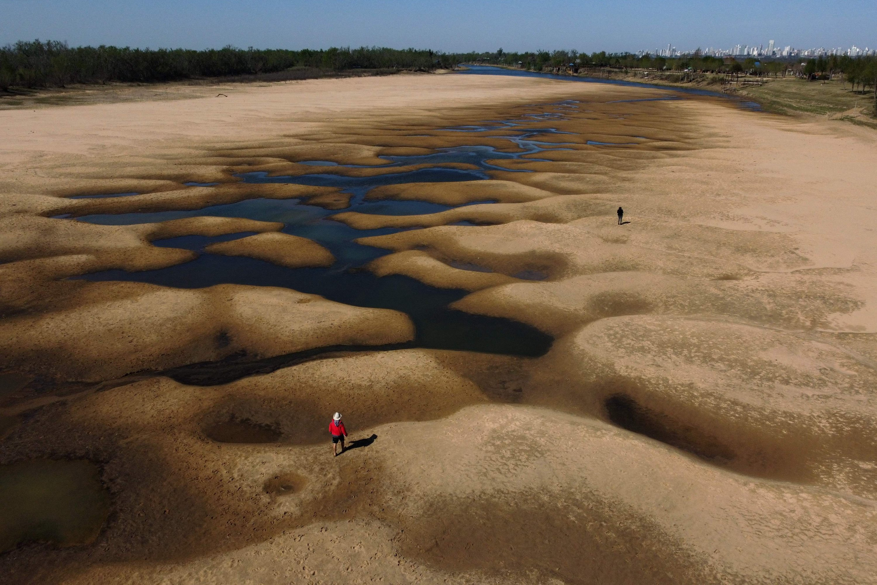 Aerial view of people walking along an almost dry arm of the Parana river, during a historic downspout, near Rosario, Santa Fe, Argentina, Aug. 22, 2021.