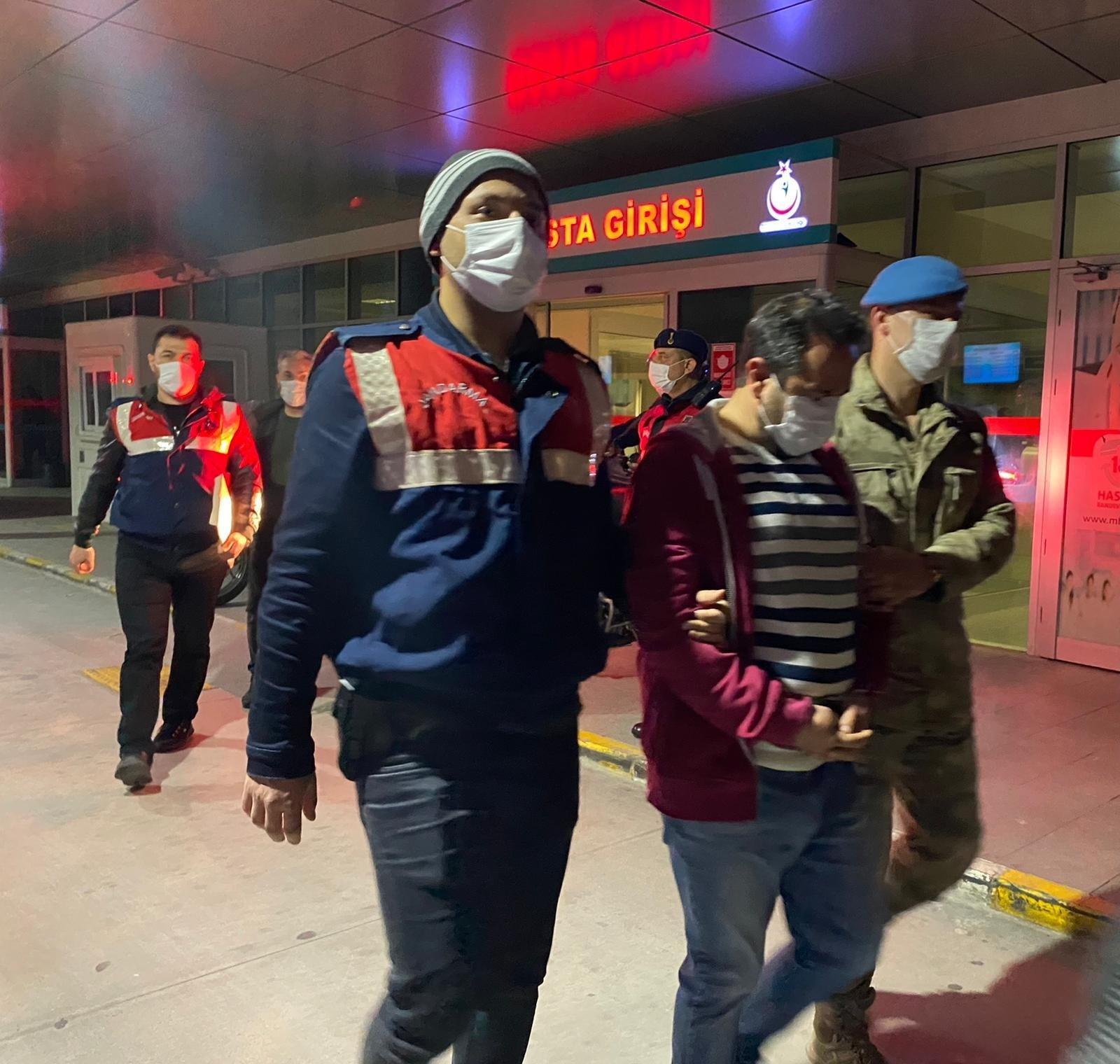 Police officers escort the captured FETÖ suspect, Izmir, Turkey, March 25, 2021. (AA PHOTO)
