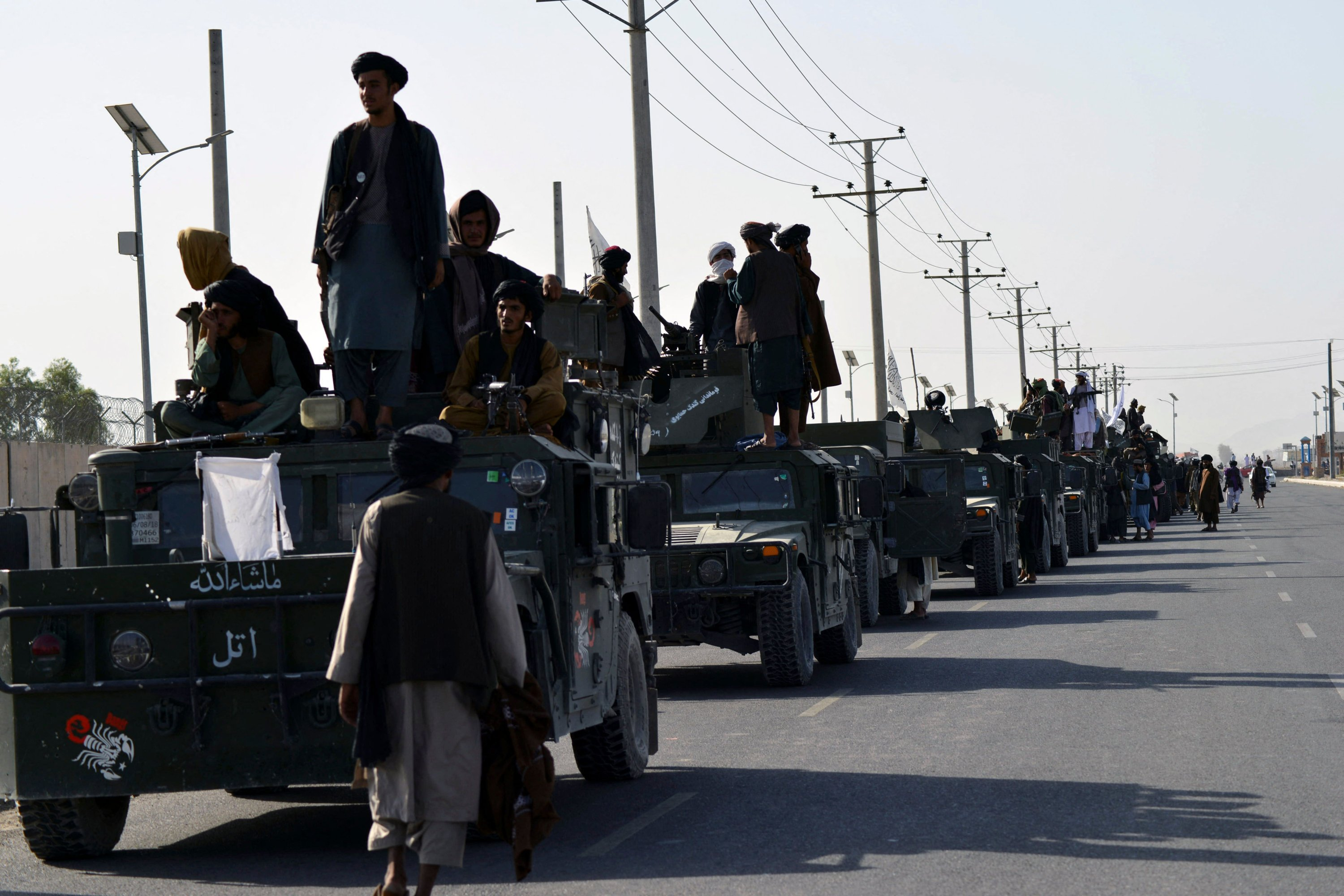 Taliban fighters atop Humvee vehicles prepare before parading along a road to celebrate after the U.S. pulled all its troops out of Afghanistan, in Kandahar, Afghanistan, Sept. 1, 2021. (Photo by Javed Tanveer via AFP)
