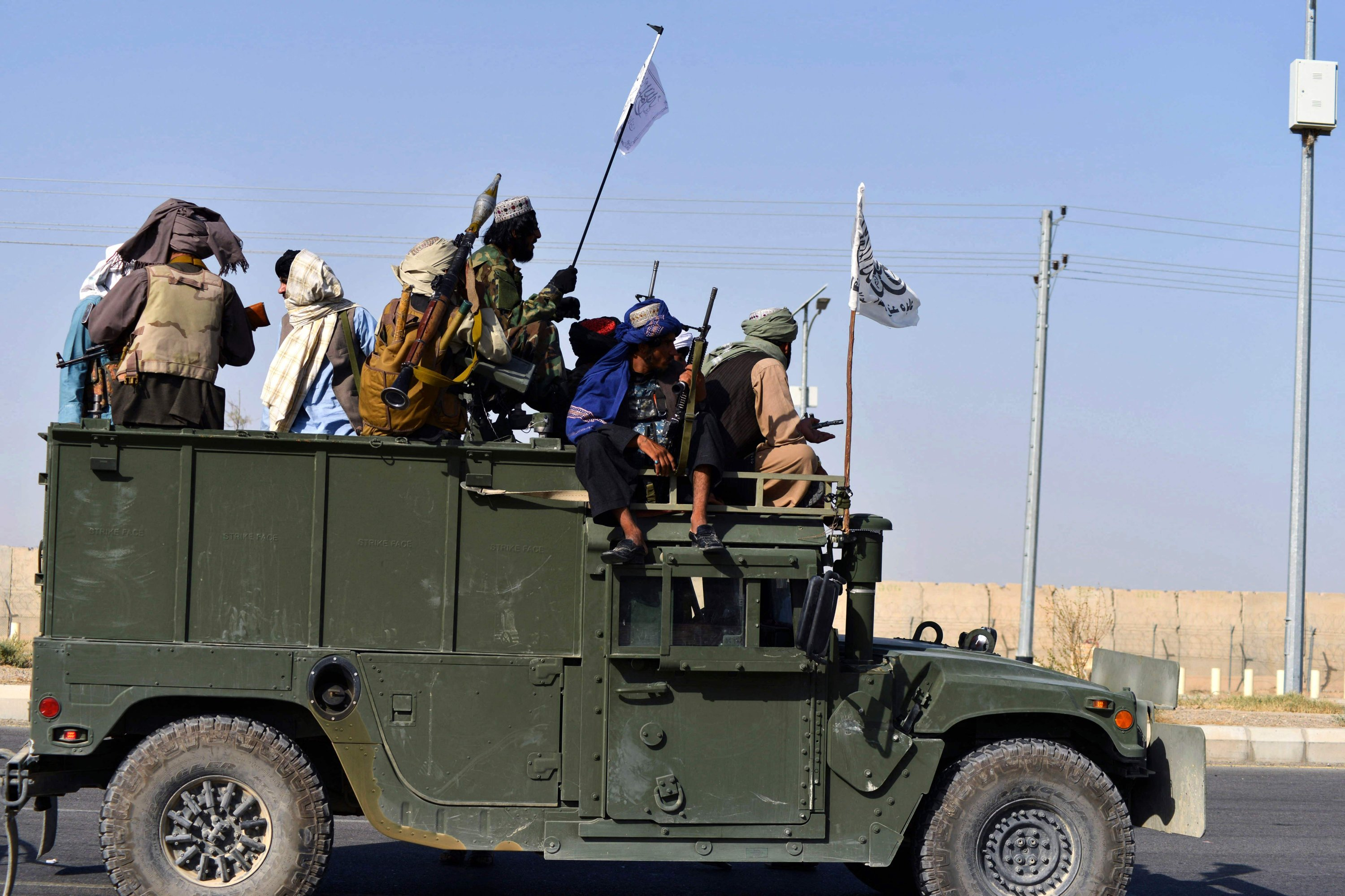 Taliban fighters stand on an armored vehicle before parading along a road to celebrate after the U.S. pulled all its troops out of Afghanistan, in Kandahar, Afghanistan, Sept. 1, 2021. (Photo by Javed Tanveer via AFP)