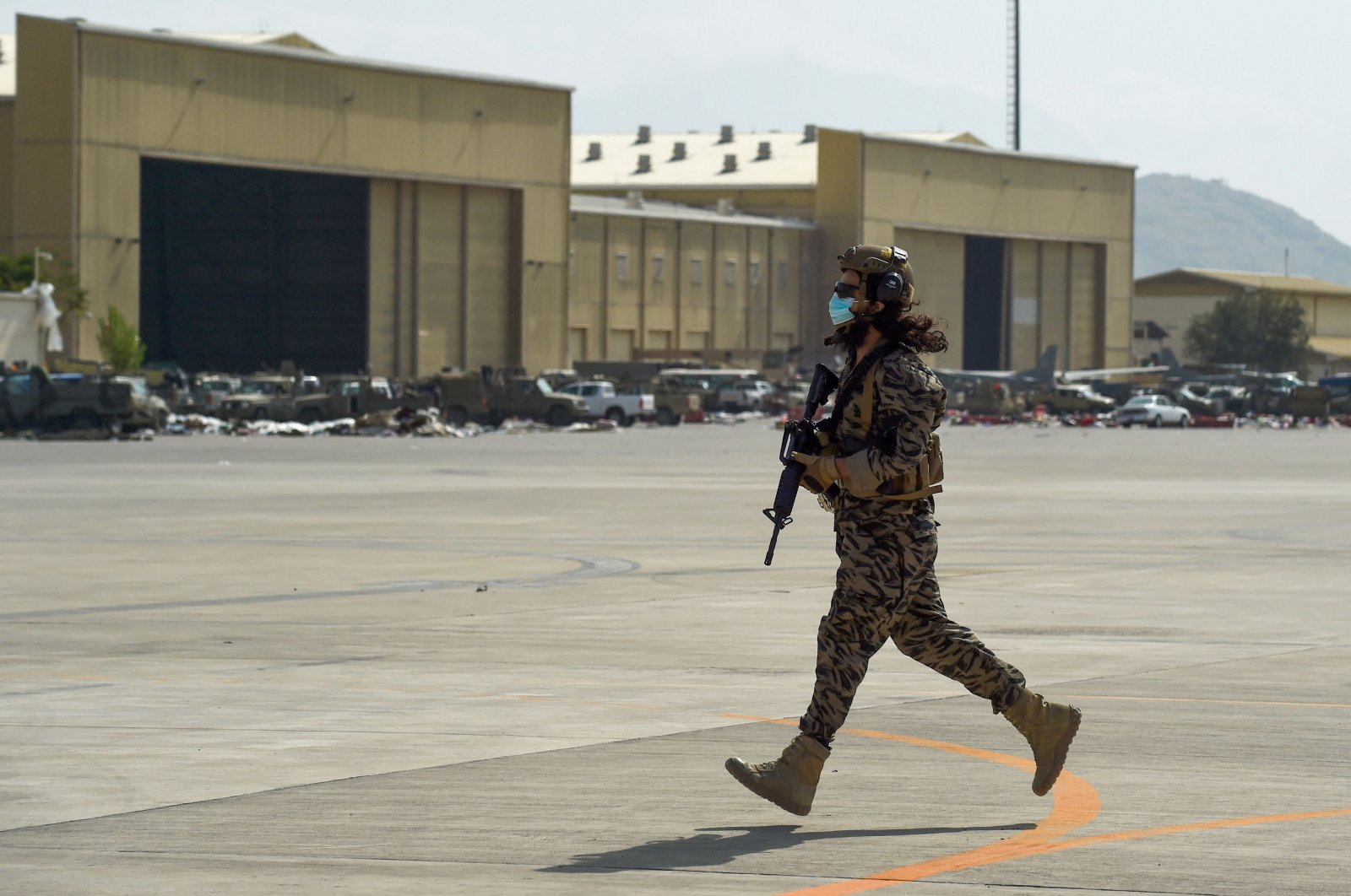 A member of the Taliban Badri 313 military unit runs to take up his position at Kabul airport after the U.S. pulled all its troops out of the country to end a 20-year war, Kabul, Afghanistan, Aug. 31, 2021. (AFP Photo)