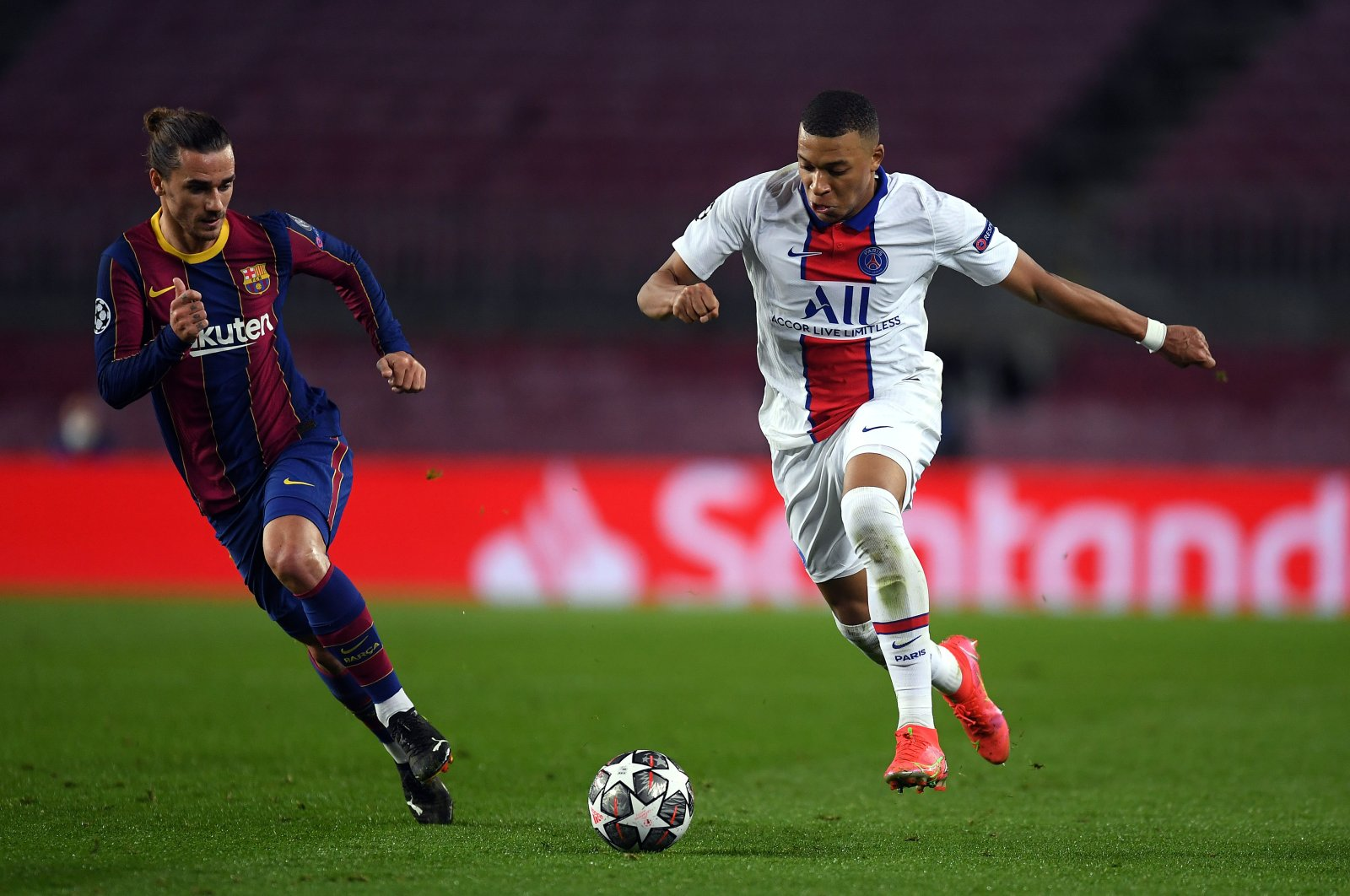 PSG's Kylian Mbappe tries to go past Barcelona's Antoine Griezmann during a Champions League Round of 16 match at Camp Nou, Barcelona, Spain, Feb. 16, 2021. (Getty Images)