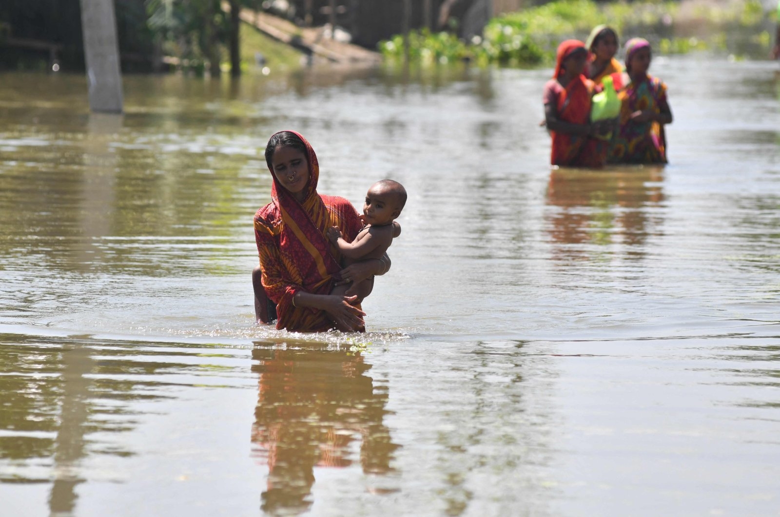 A woman carrying her child wades along a road in a flood-affected area following heavy monsoon rainfalls in Morigaon district in India's Assam state, Aug. 31, 2021. (AFP Photo)