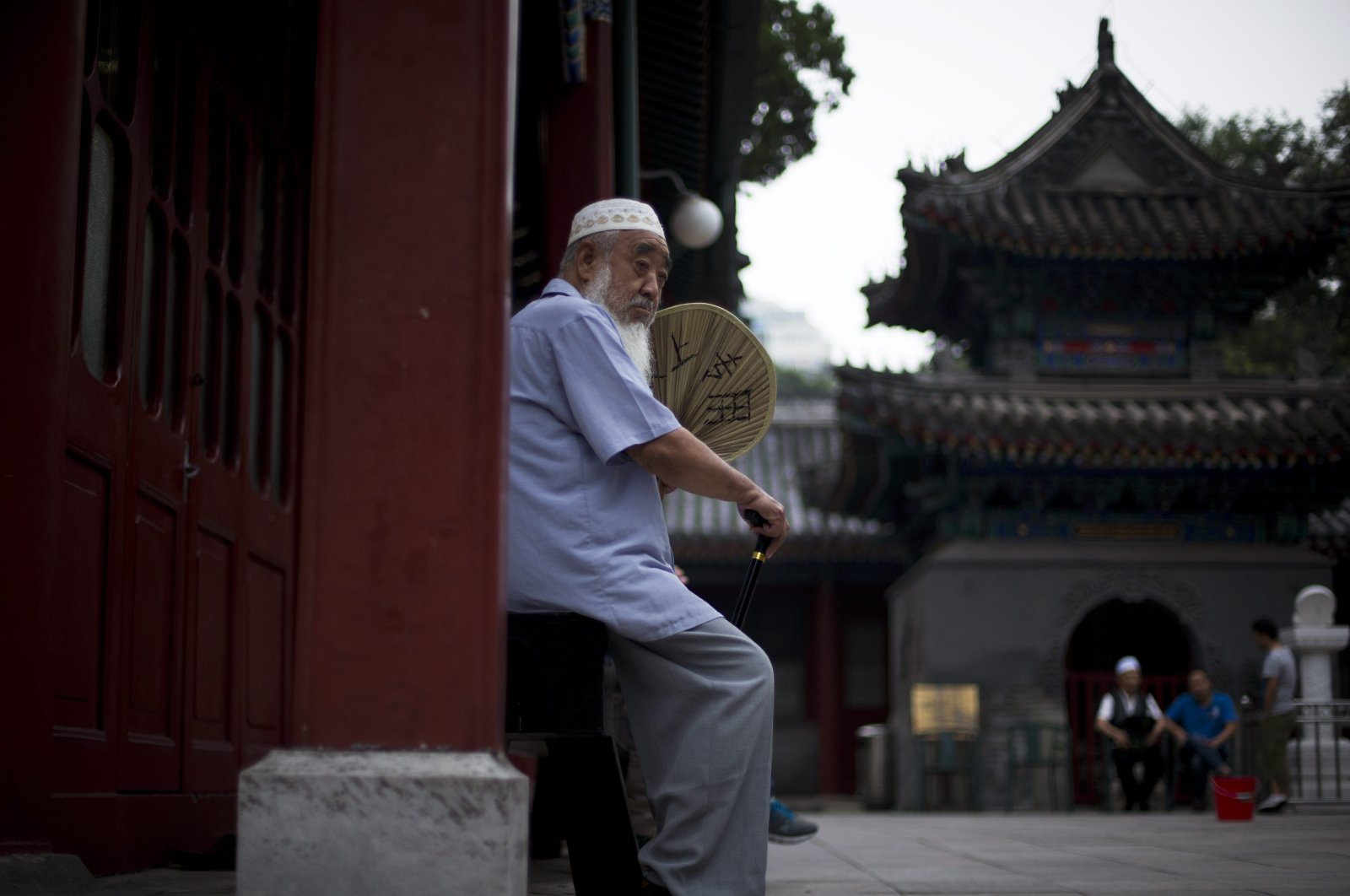 A Chinese Muslim man fans himself as he waits for the time to break his fast during the Muslim holy month of Ramadan at the Niujie mosque, the oldest and largest mosque in Beijing, China, July 2, 2014. (AP Photo)