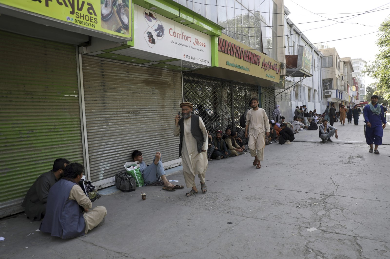 Afghans line a mostly shuttered market for hours to try to withdraw money from a nearby bank, in Kabul, Afghanistan,  Aug. 15, 2021. (AP Photo)