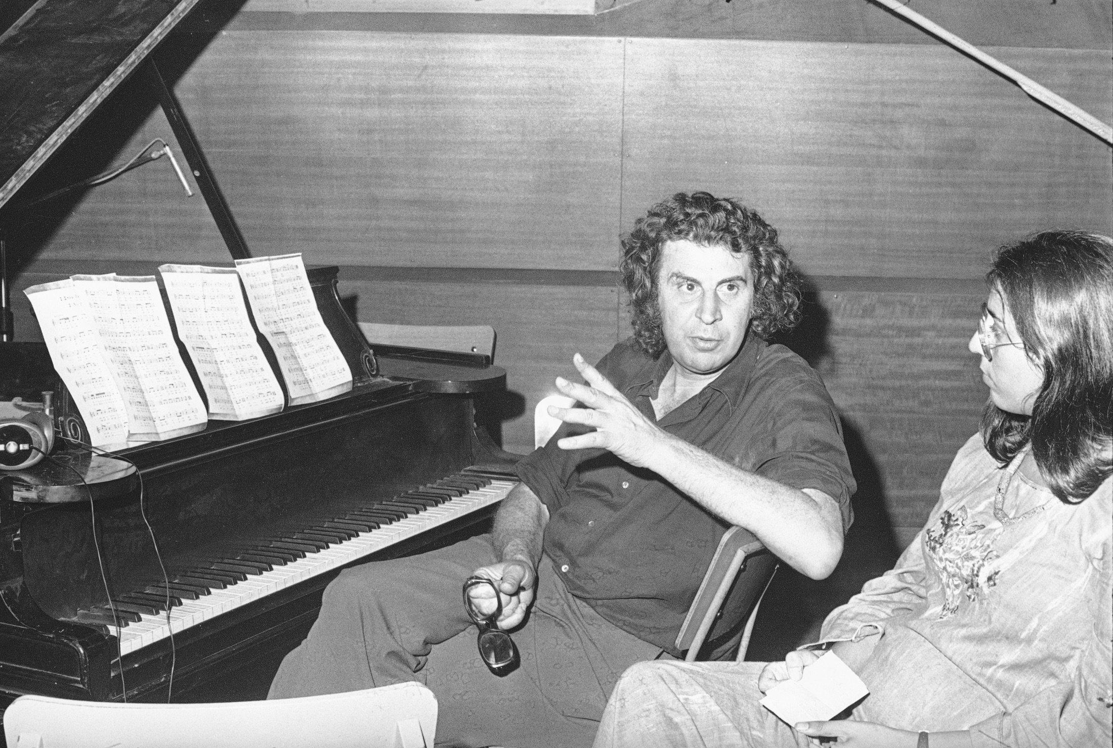Greek composer Mikis Theodorakis (C) talks with Greece's top singer Maria Farandouri during a break at the Athens recording studio, Athens, Greece, Aug. 21, 1974. (AP Photo)