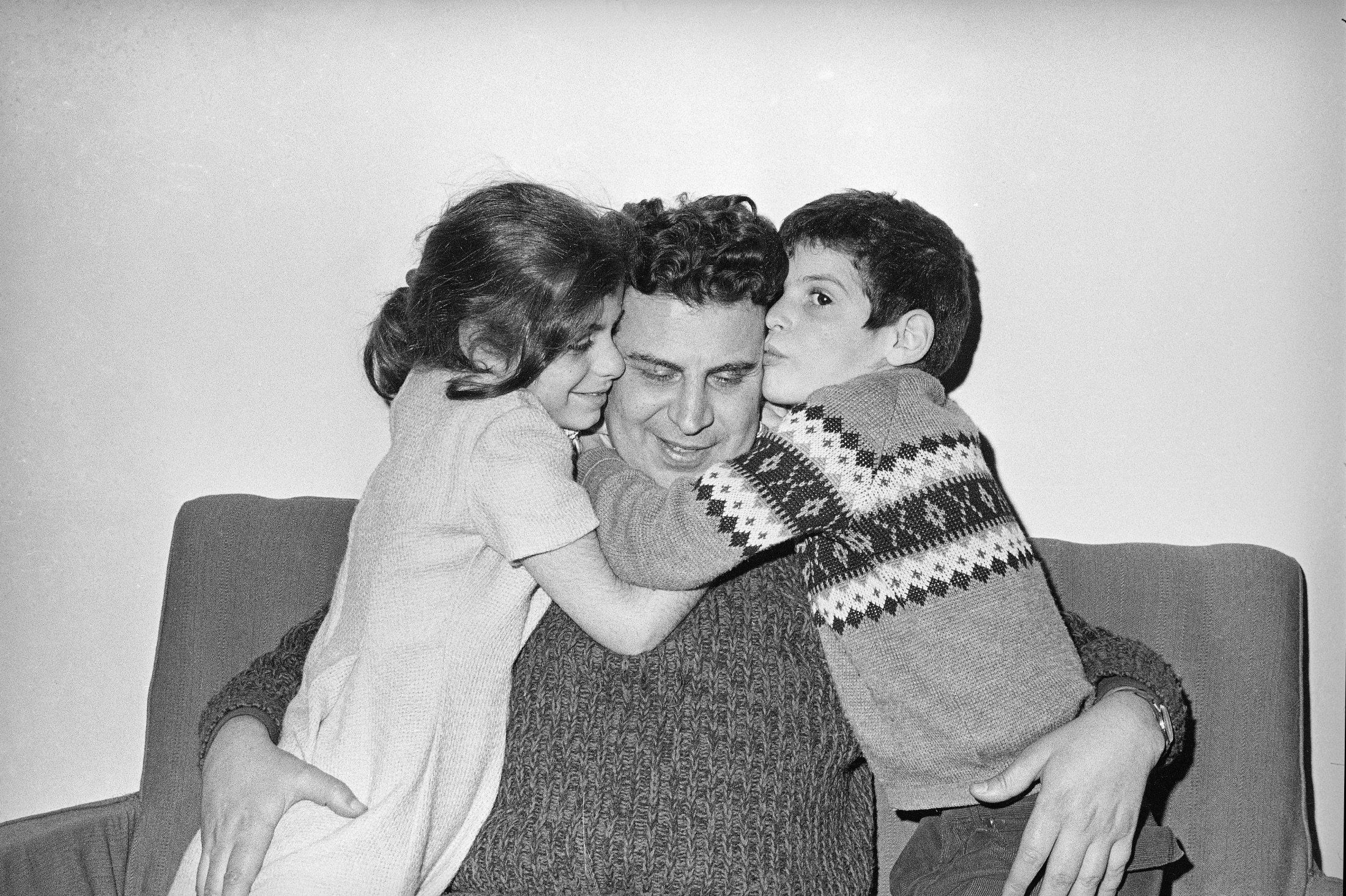 Greek composer Mikis Theodorakis (C) is hugged by his children, Margarita (L), and Giorgios, after his release from prison in Athens, Greece, Jan. 27, 1968. (AP Photo)