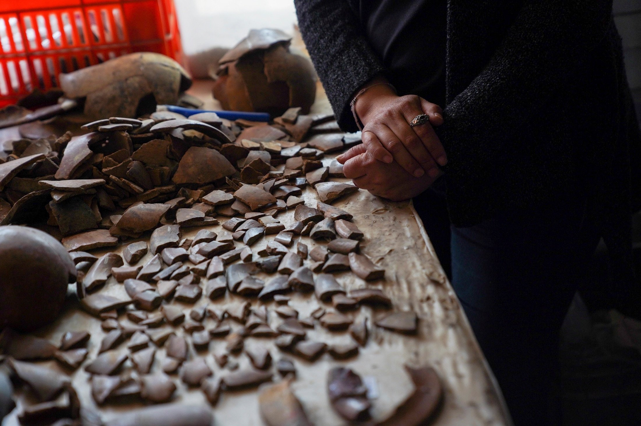 A worker arranges pieces of objects found inside a 2,000-year-old tunnel built under the ornate Feathered Serpent Pyramid, in the ruins of Teotihuacan, in San Juan Teotihuacan, Mexico, Aug. 12, 2021. (Reuters Photo)