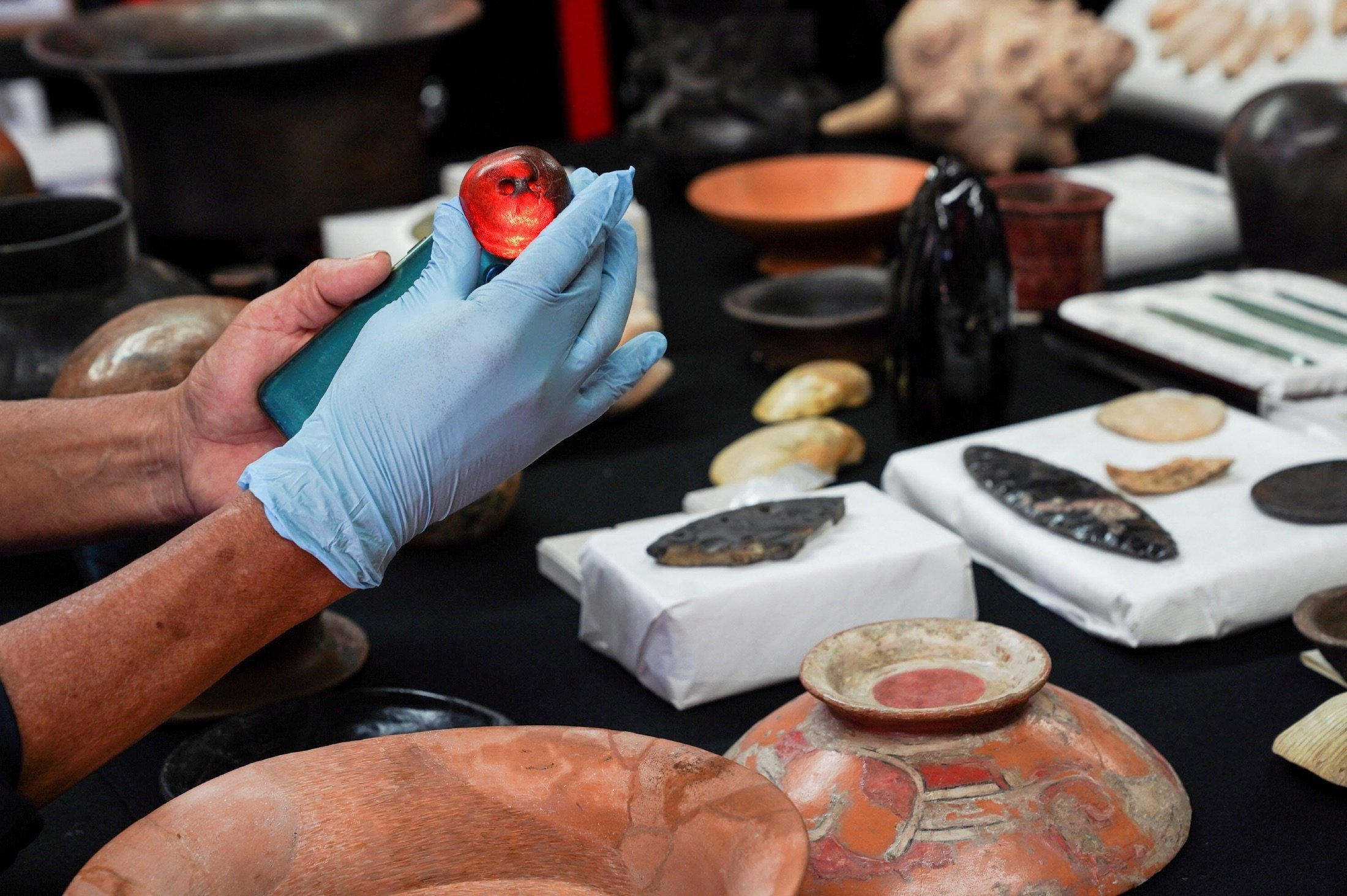 Archaeologist Sergio Gomez holds a carved amber sphere found inside a 2,000-year-old tunnel built under the ornate Feathered Serpent Pyramid, in the ruins of Teotihuacan, in San Juan Teotihuacan, Mexico, Aug. 12, 2021. (Reuters Photo)