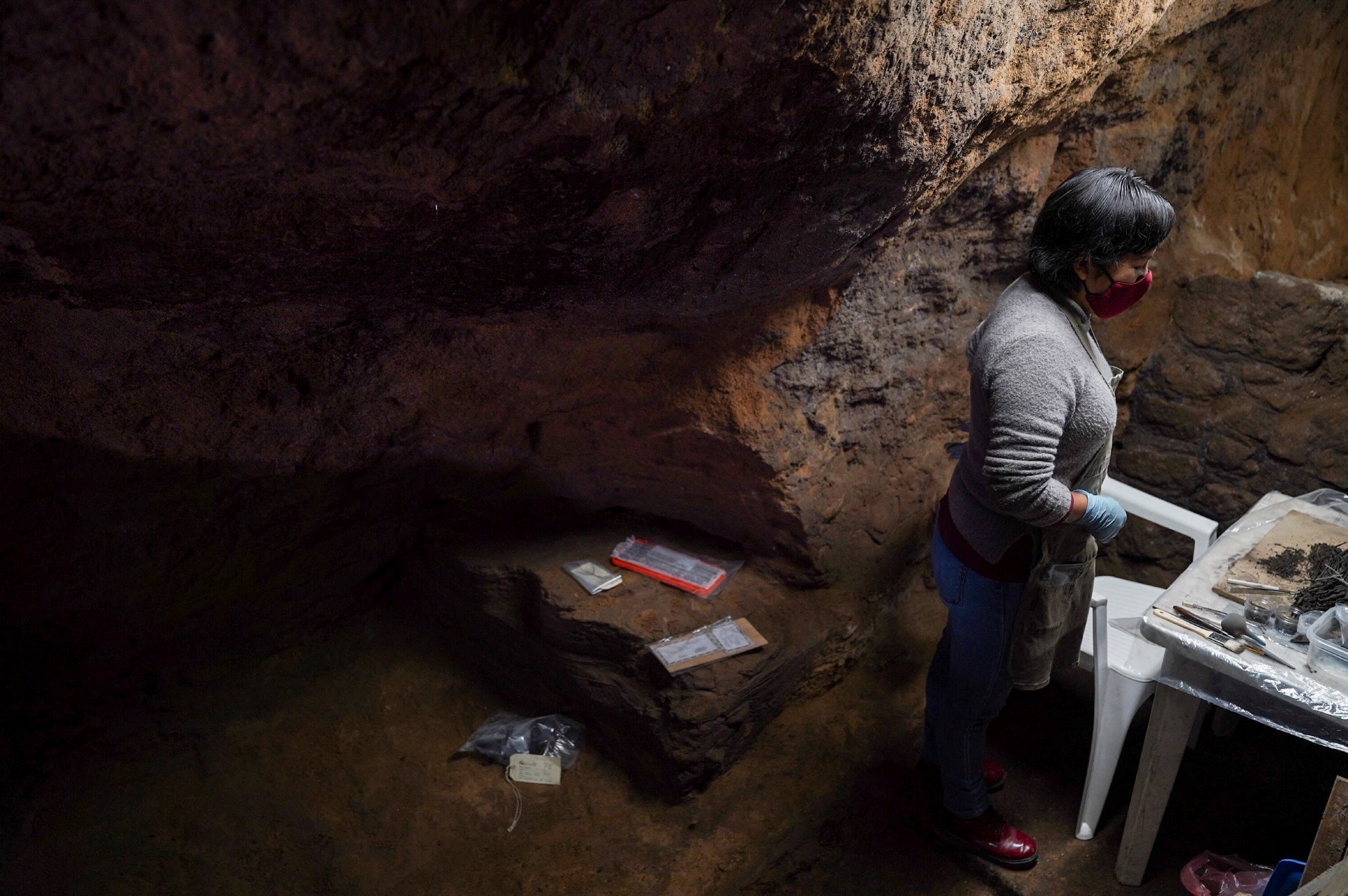 Sonia Disciplina examines a bouquet of 'well-preserved old flowers' inside inside a 2,000-year-old tunnel built under the ornate Feathered Serpent Pyramid, in the ruins of Teotihuacan, in San Juan Teotihuacan, Mexico, Aug. 12, 2021. (Reuters Photo)