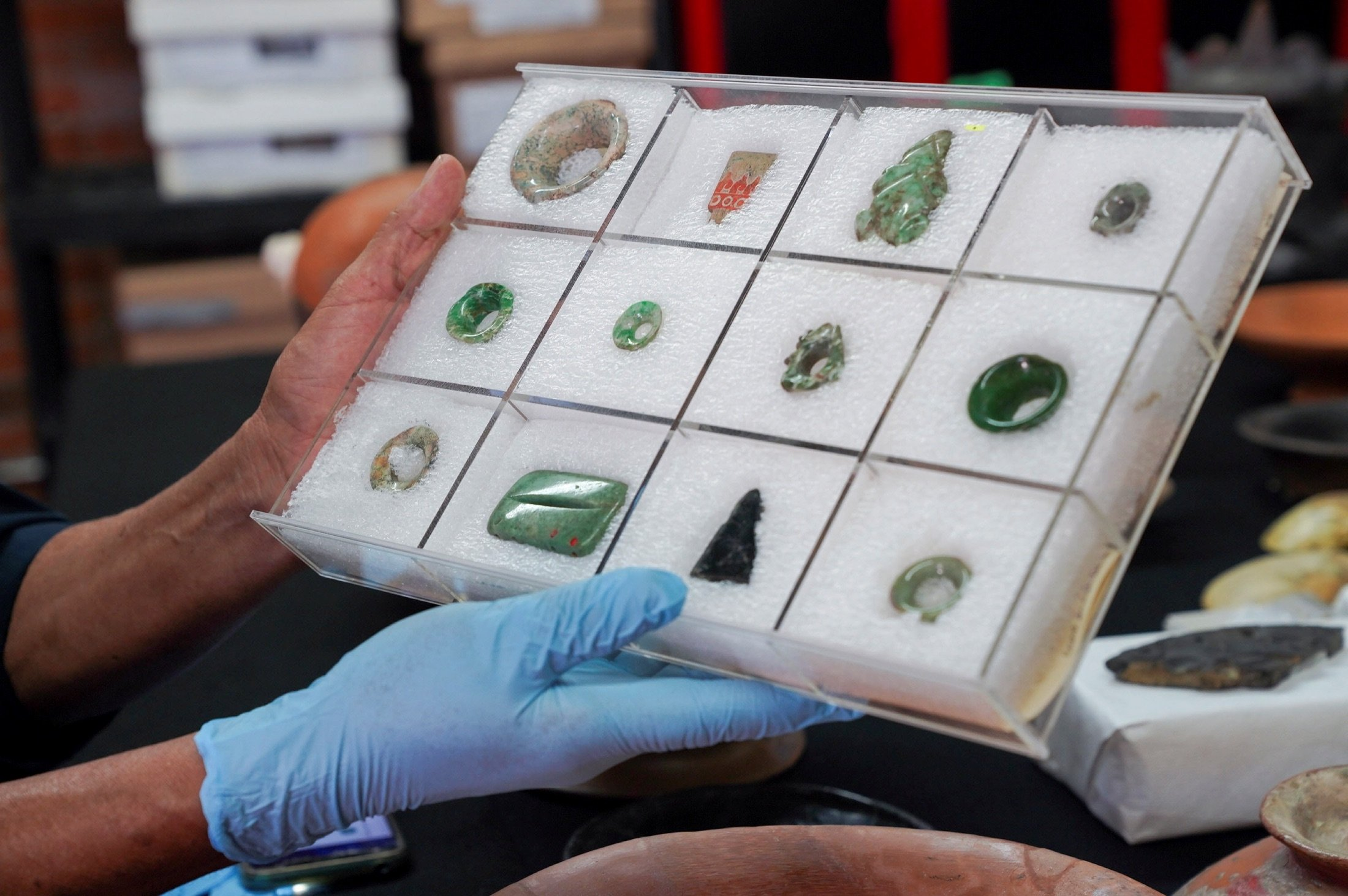Archaeologist Sergio Gomez displays jade jewelry, including ear spools and pendants, found inside a 2,000-year-old tunnel built under the ornate Feathered Serpent Pyramid, in the ruins of Teotihuacan, in San Juan Teotihuacan, Mexico, Aug. 12, 2021. (Reuters Photo)
