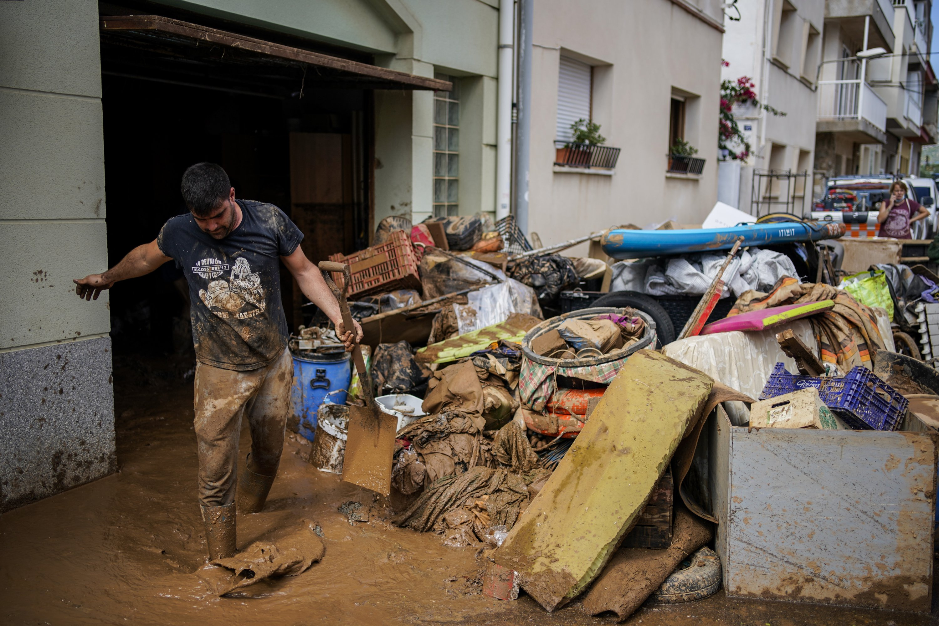 A man cleans up mud after flooding in a seaside town of Alcanar, in northeastern Spain, Sept. 2, 2021. (AP Photo)