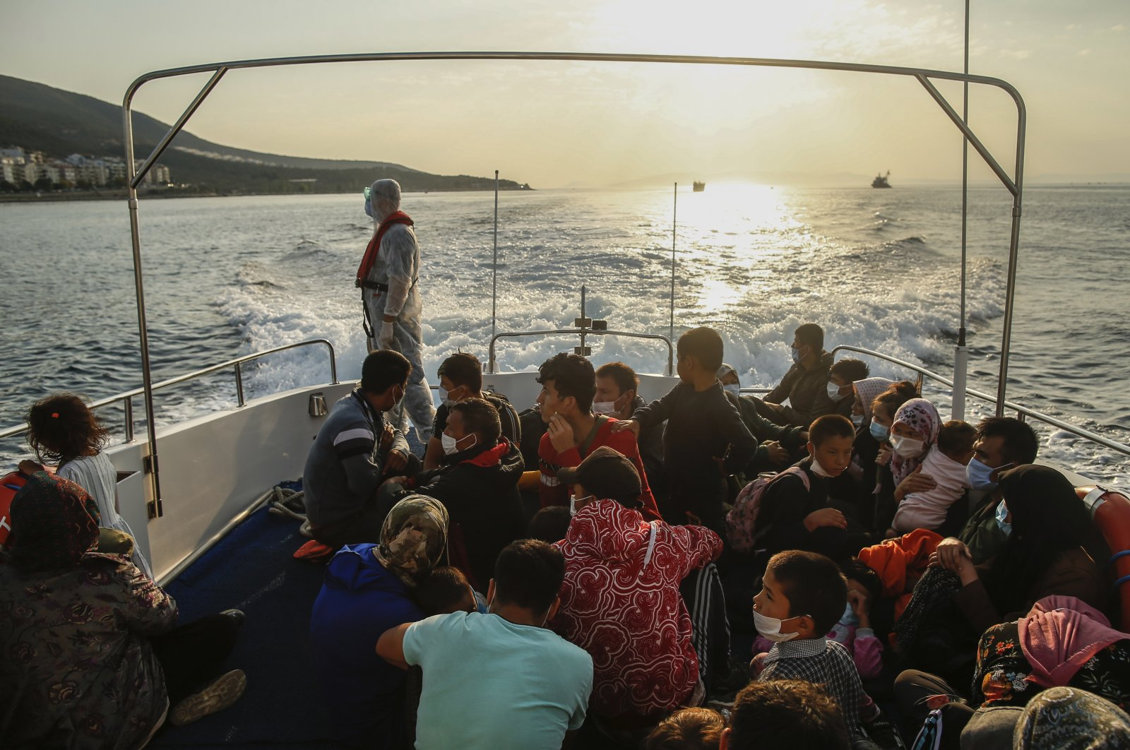 Migrants sit on a Turkish coast guard vessel after they were pushed back by the Greek coast guard, Saturday, Sept. 12, 2020. (AP File Photo)