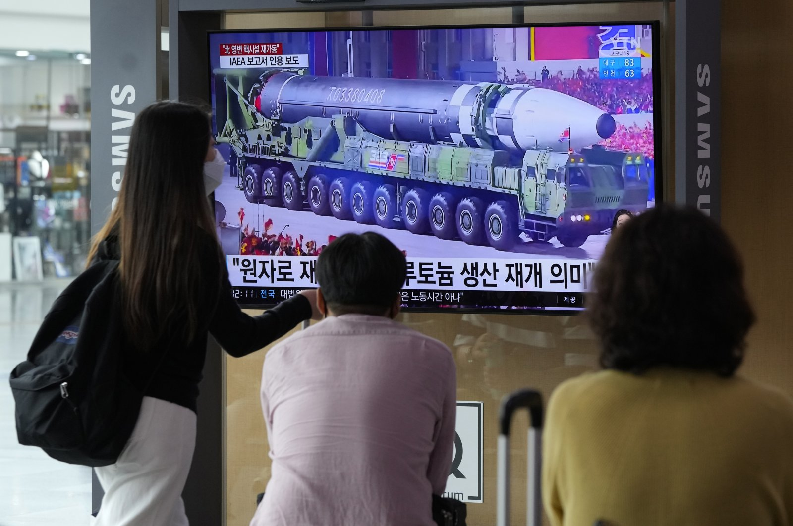 People watch a TV screen showing a file image of a North Korean missile in a military parade during a news program at the Seoul Railway Station in Seoul, South Korea, Aug. 30, 2021. (AP Photo)
