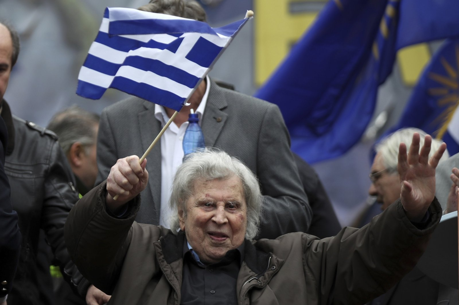Famous Greek composer Mikis Theodorakis waves a Greek flag after his speech at a rally in Athens, Greece, Feb. 4, 2018. (AP Photo)