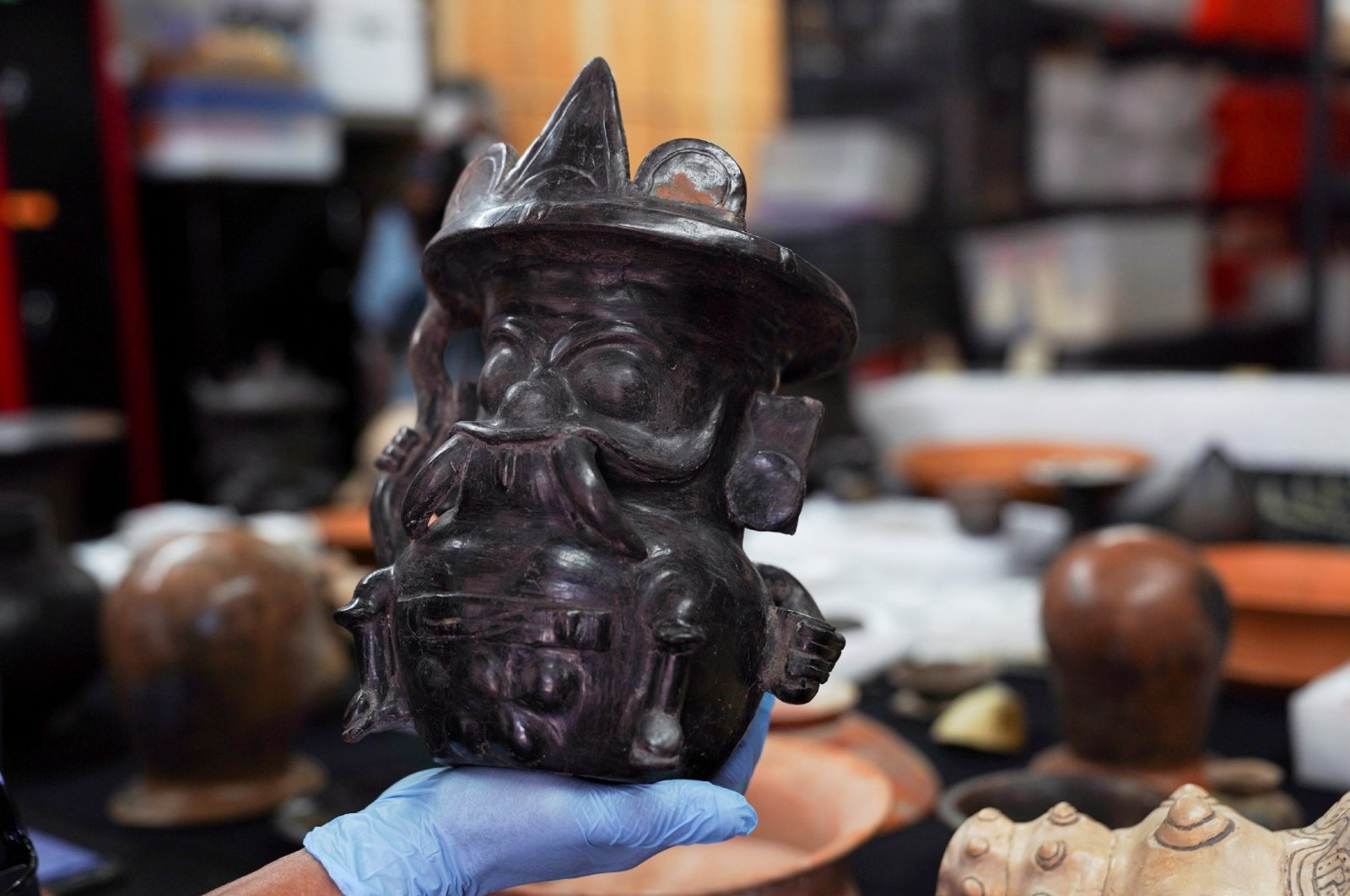 Archaeologist Sergio Gomez displays a pot shaped in the image of storm god Tlaloc, found inside a 2,000-year-old tunnel built under the ornate Feathered Serpent Pyramid, in the ruins of Teotihuacan, in San Juan Teotihuacan, Mexico, Aug. 12, 2021. (Reuters Photo)