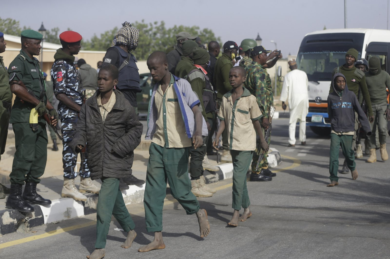 A group of schoolboys are escorted by Nigerian military and officials following their release after they were kidnapped, in Katsina, Nigeria, Dec. 18, 2020. (AP Photo)
