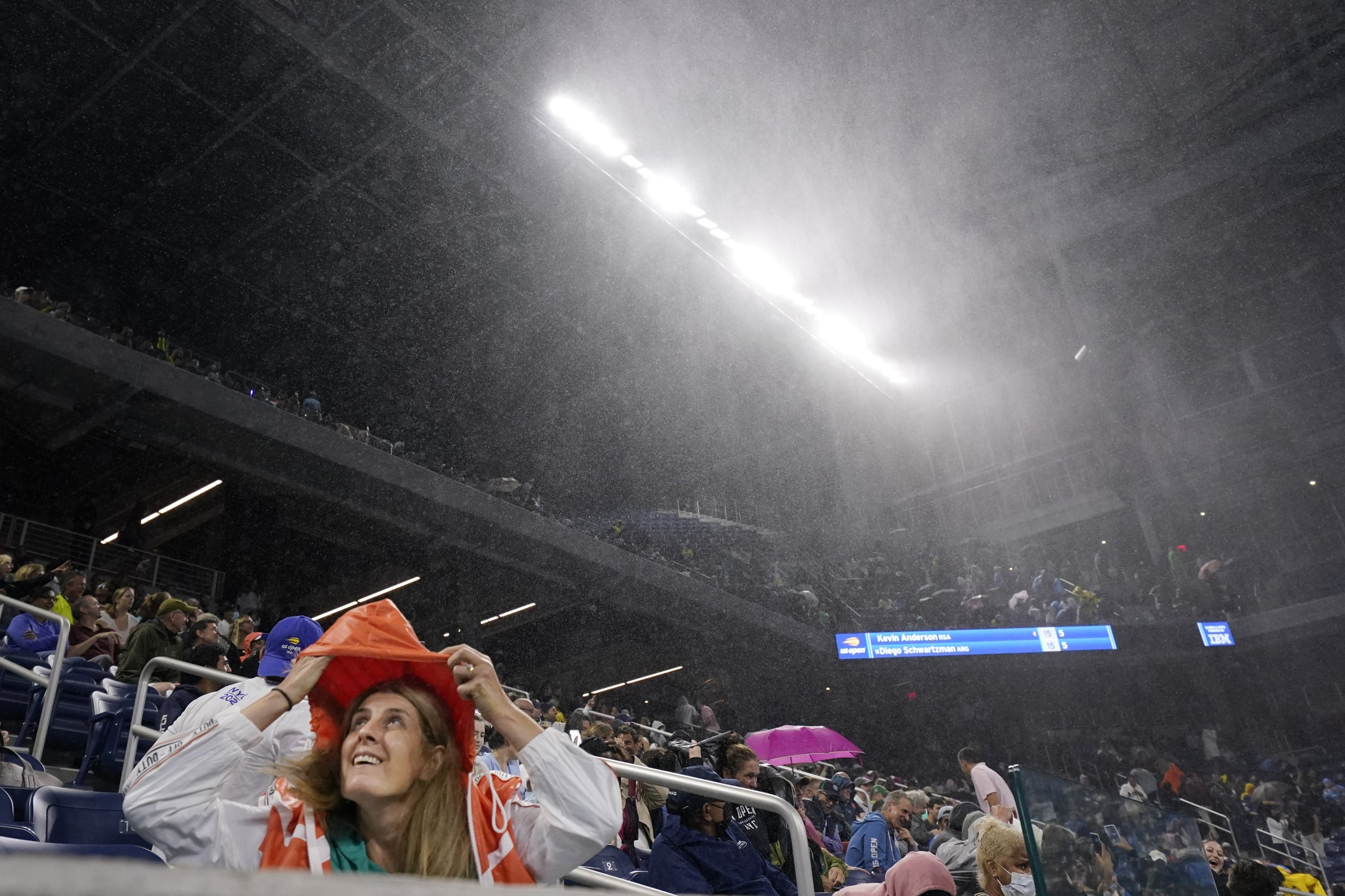 A fan covers herself from rain in Louis Armstrong Stadium during a match U.S. Open second-round match, New York, U.S., Sept. 1, 2021. (AP Photo)