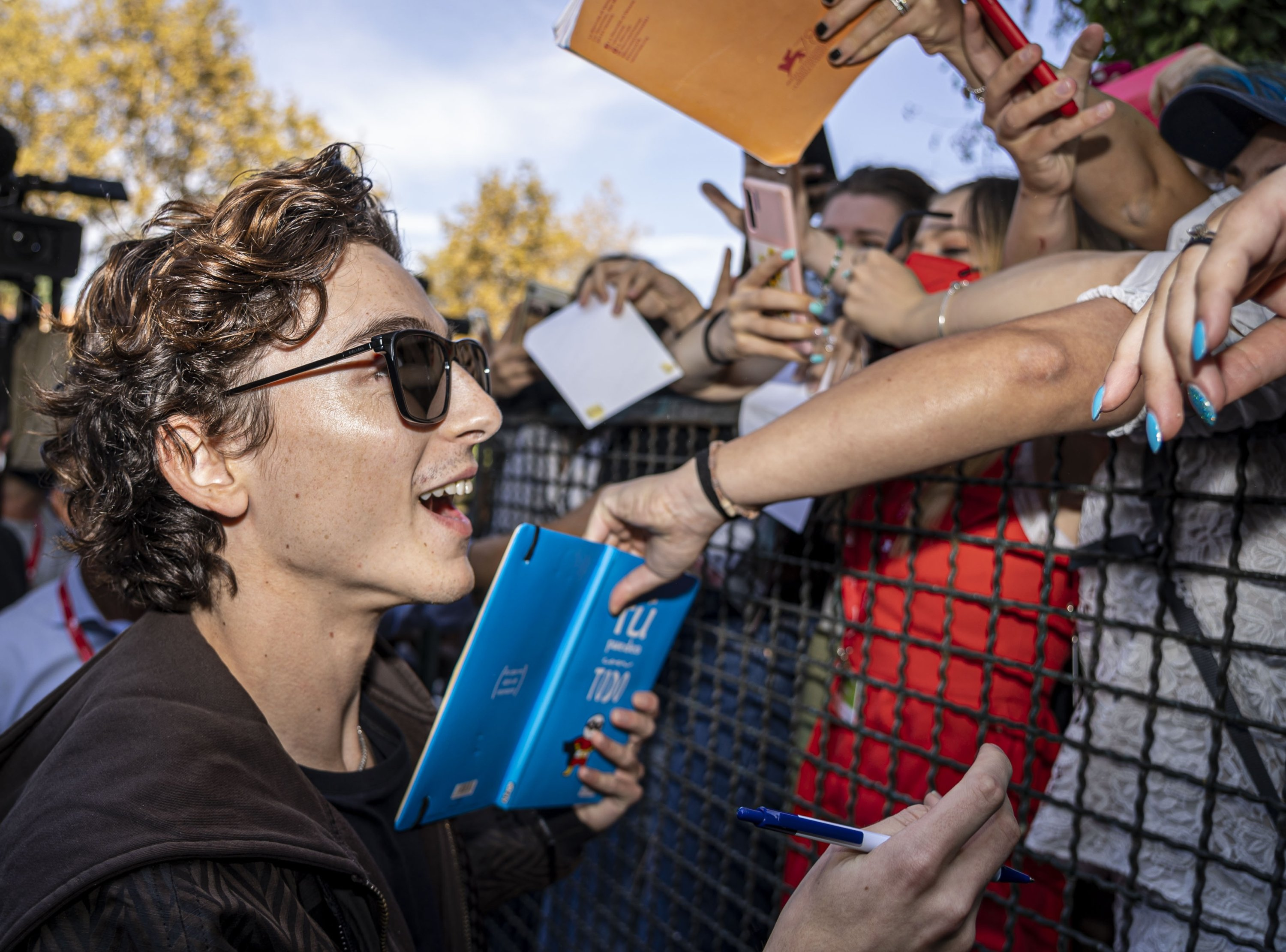 """Actor Timothee Chalamet signs autographs upon arrival for the photocall of the film """"Dune"""" at the 78th Venice Film Festival, in Venice, Italy, Sept. 3, 2021. (AP Photo)"""
