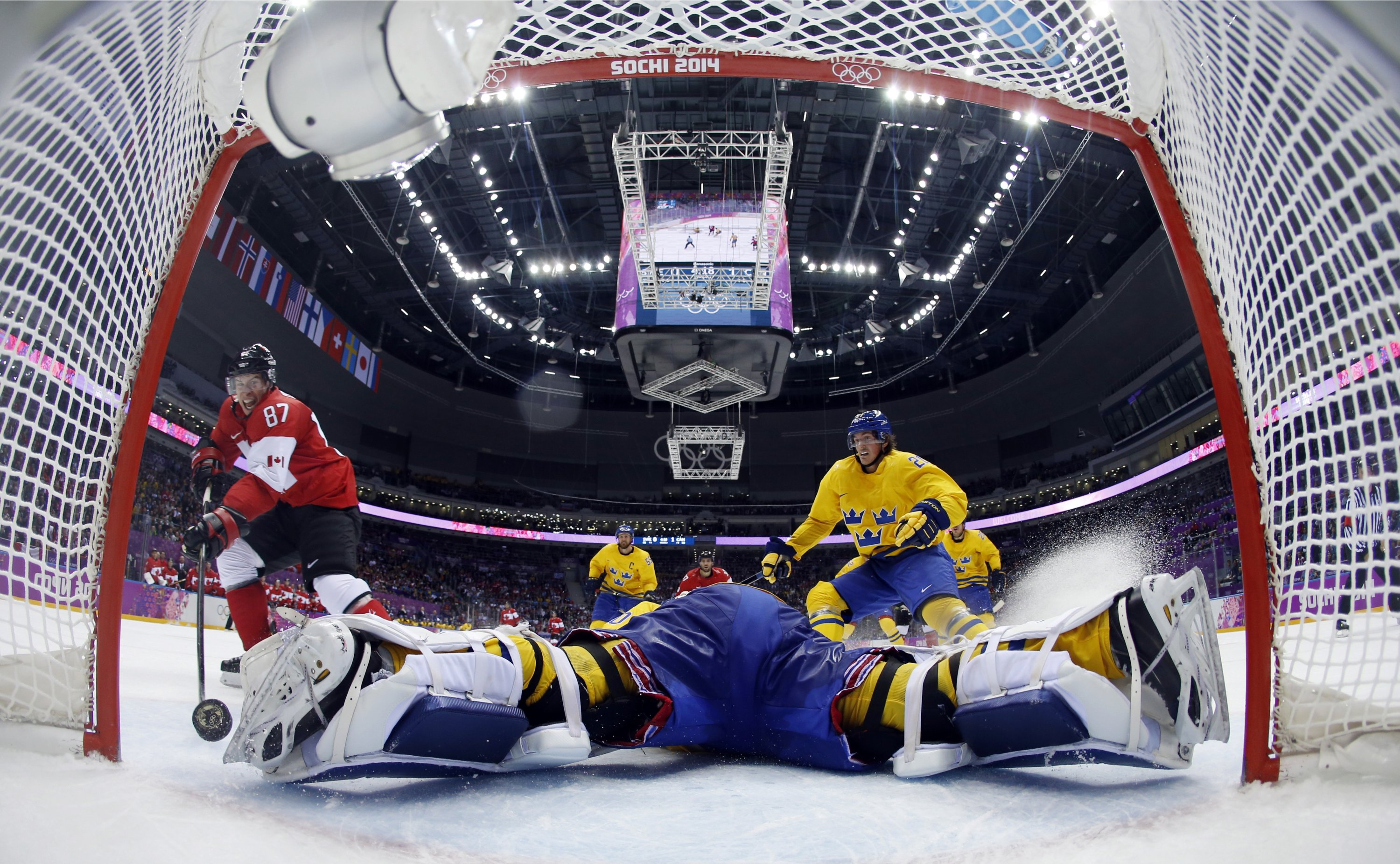 Canada forward Sidney Crosby (L) scores a goal past Sweden goaltender Henrik Lundqvist during the second period of the men's gold medal ice hockey game at the 2014 Winter Olympics in Sochi, Russia, Feb. 23, 2014. (AP File Photo)