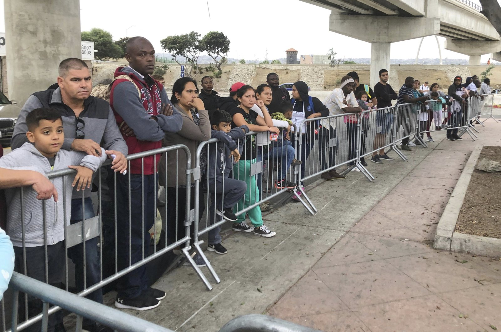 Asylum seekers in Tijuana, Mexico, listen to names being called from a waiting list to claim asylum at a border crossing in San Diego, California, U.S., Sept. 26, 2019. (AP Photo)