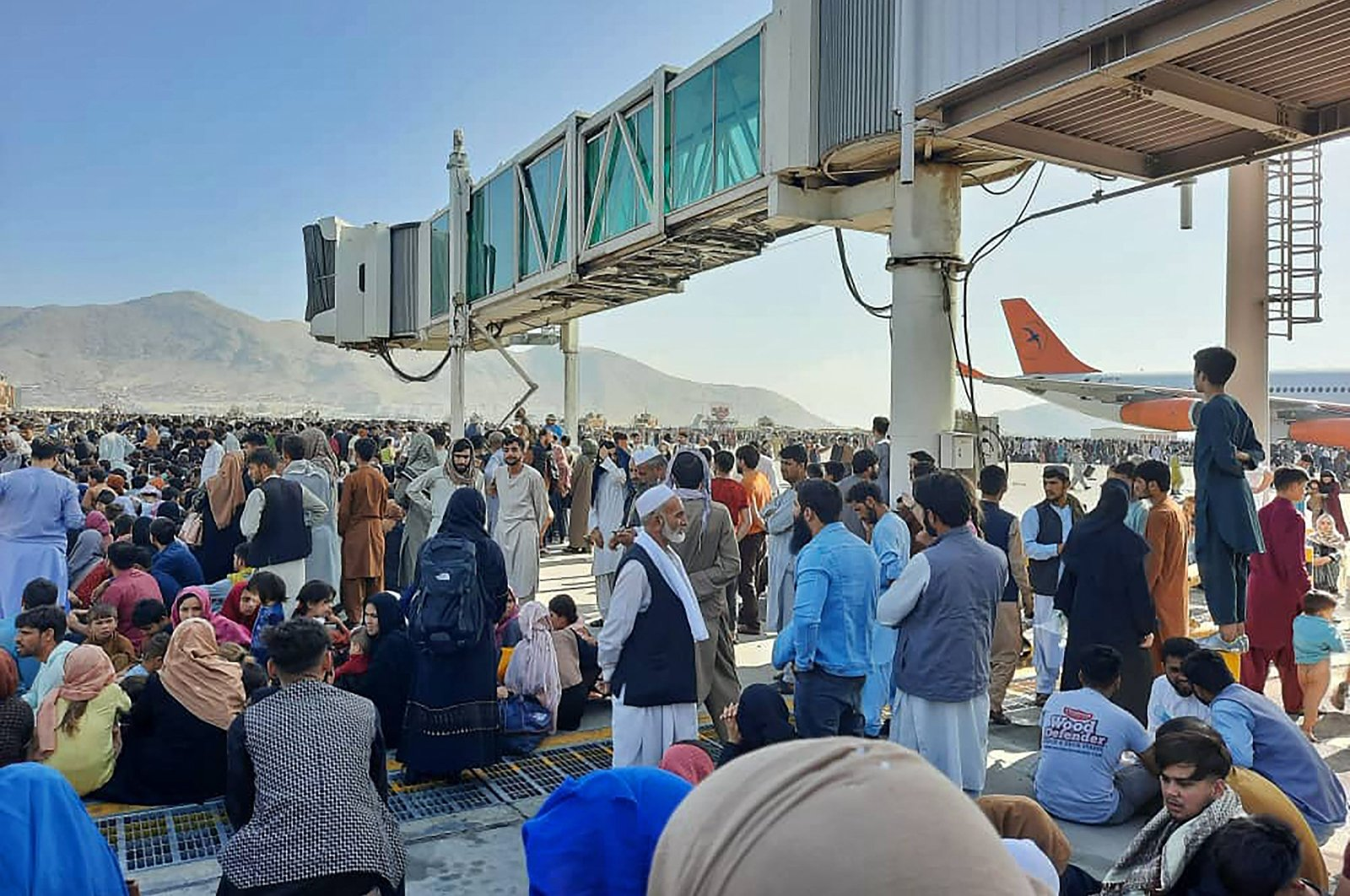 Afghans crowd at the tarmac of the Kabul Hamid Karzai International Airport on Aug. 16, 2021. (AFP)