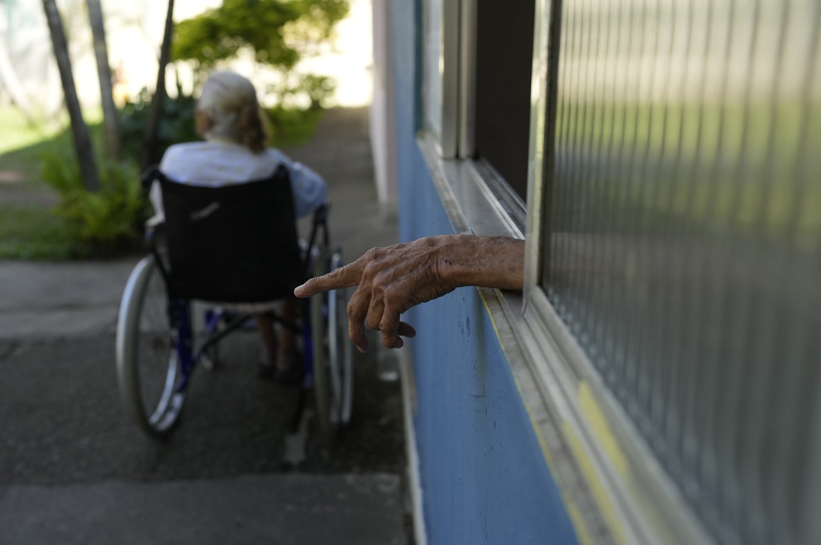 A man puts his hand out a window during a third dose COVID-19 vaccination campaign for elderly residents in long-term care institutions, at Casa de Repouso Laco de Ouro nursing home in Rio de Janeiro, Brazil, Thursday, Sept. 2, 2021. (AP Photo)