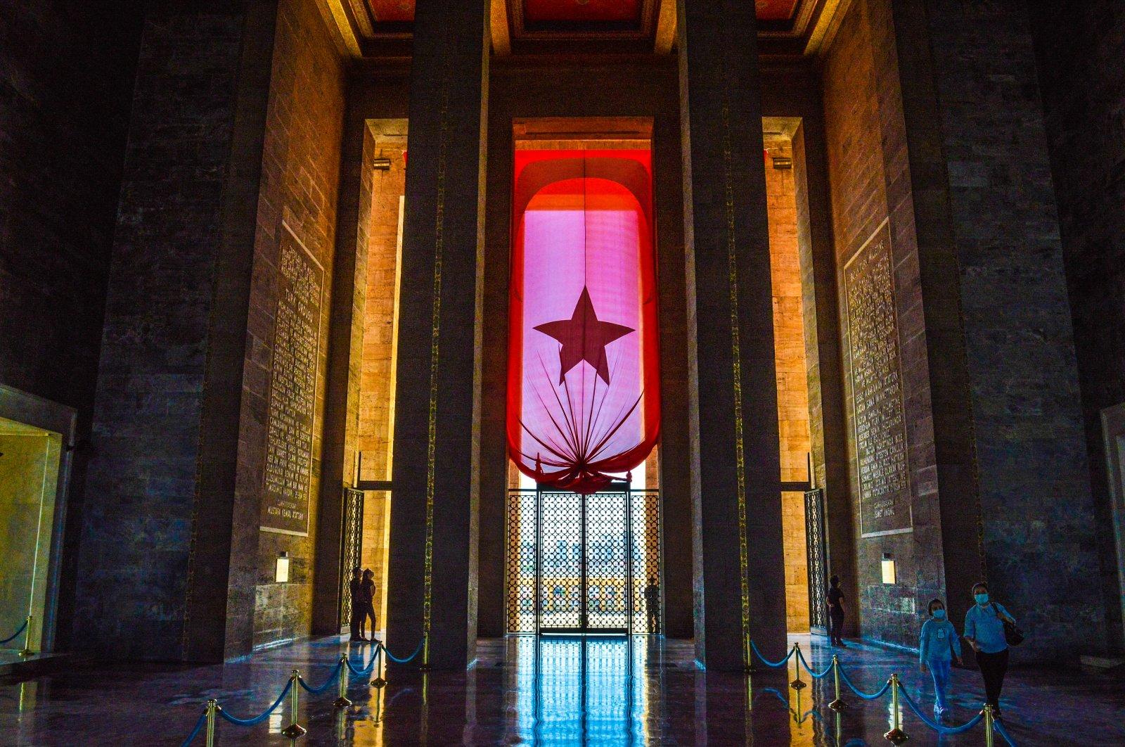 People wearing protective face masks walk past a giant Turkish national flag at Anıtkabir, the mausoleum of modern Turkey's founder Mustafa Kemal Atatürk, in Ankara, Turkey, Oct. 13, 2021. (Photo by Getty Images)