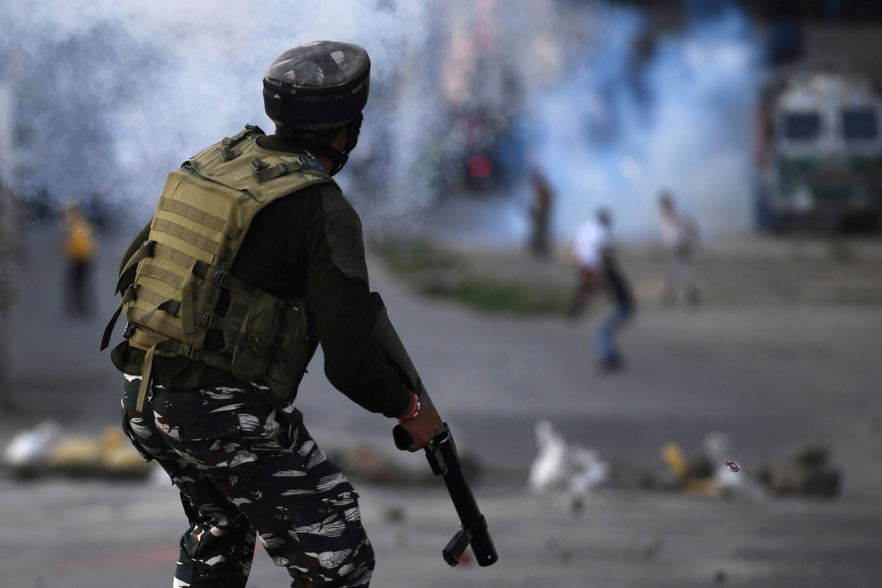 An Indian government security force personnel watches after firing tear gas in an attempt to disperse Kashmiri protesters during a clash in Srinagar, Indian-controlled Kashmir on Sept. 2, 2021 (AFP Photo)