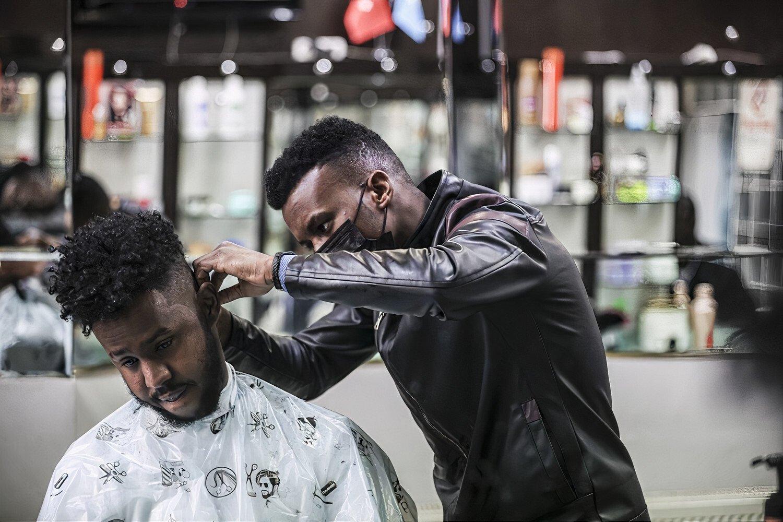 A Somali hairdresser gives a haircut to a customer in the capital Ankara, Turkey, April 12, 2021. (AA Photo)