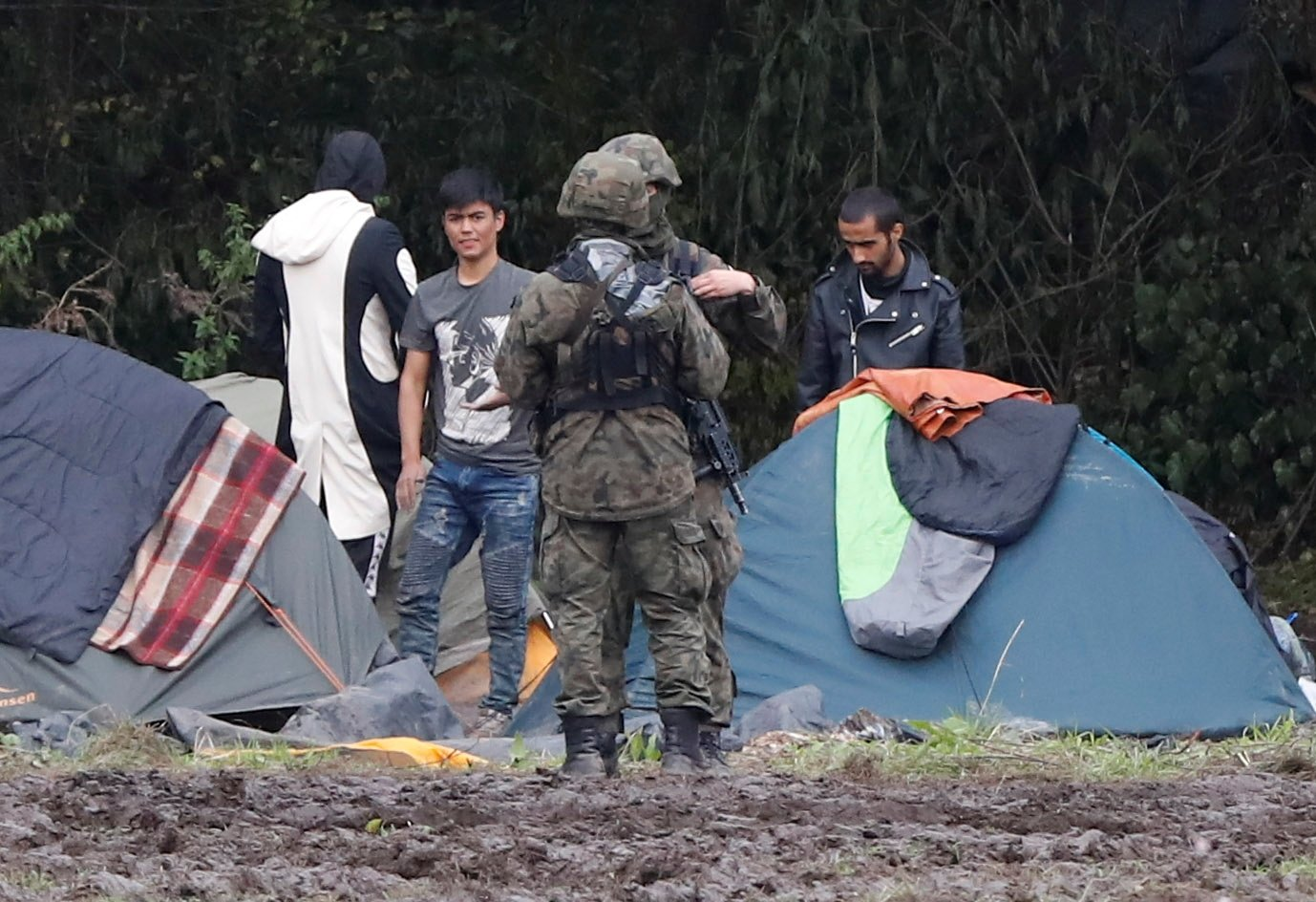 Polish border guard officers stand guard next to a group of migrants stranded on the border between Belarus and Poland near the village of Usnarz Gorny, Poland, Sept. 1, 2021. (Reuters Photo)