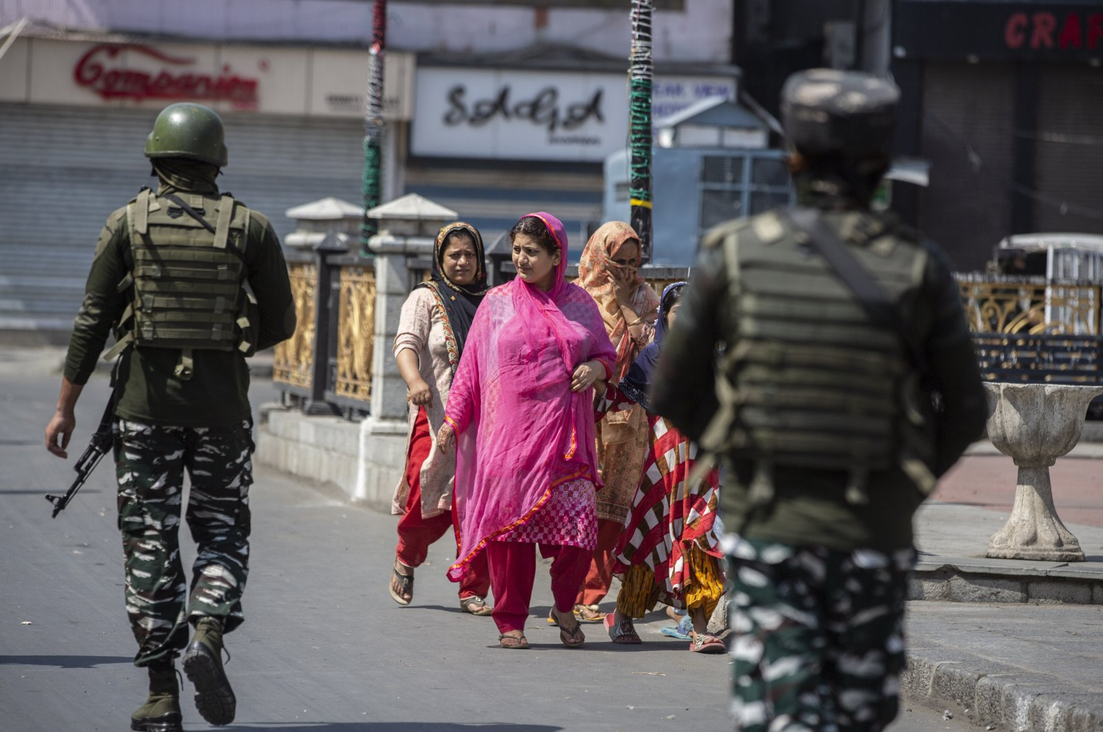 Indian paramilitary soldiers patrol as civilians walk in a deserted market area in Srinagar, Indian-controlled Kashmir, Sept. 2, 2021. (AP Photo)