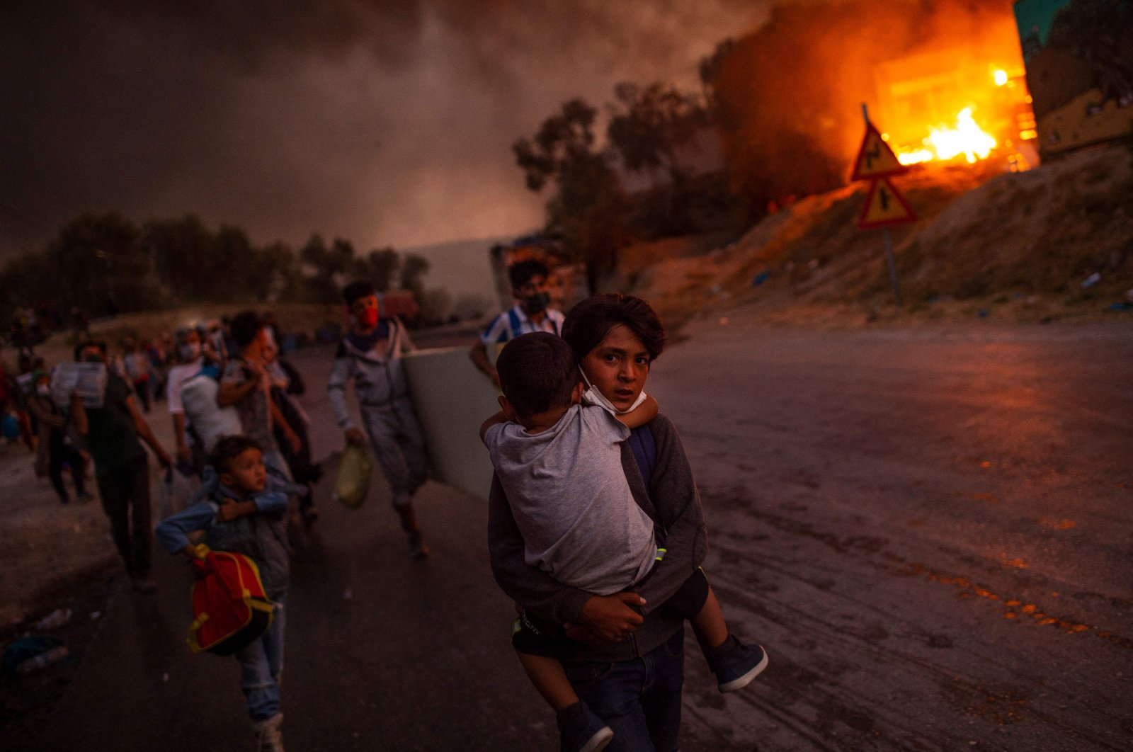 A boy carries a child in his arms as migrants flee the Moria camp after a fire broke out, on the island of Lesbos, Sept. 9, 2020. (AFP Photo)