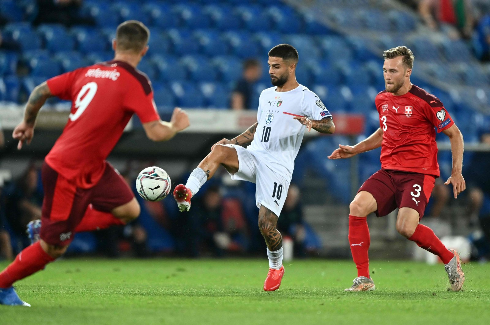 Italy's Lorenzo Insigne (C) controls the ball next to Switzerland's defender Silvan Widmer (R) during the World Cup 2022 qualifier at St. Jakob-Park stadium in Basel, Switzerland, Sept. 5, 2021. (AFP Photo)