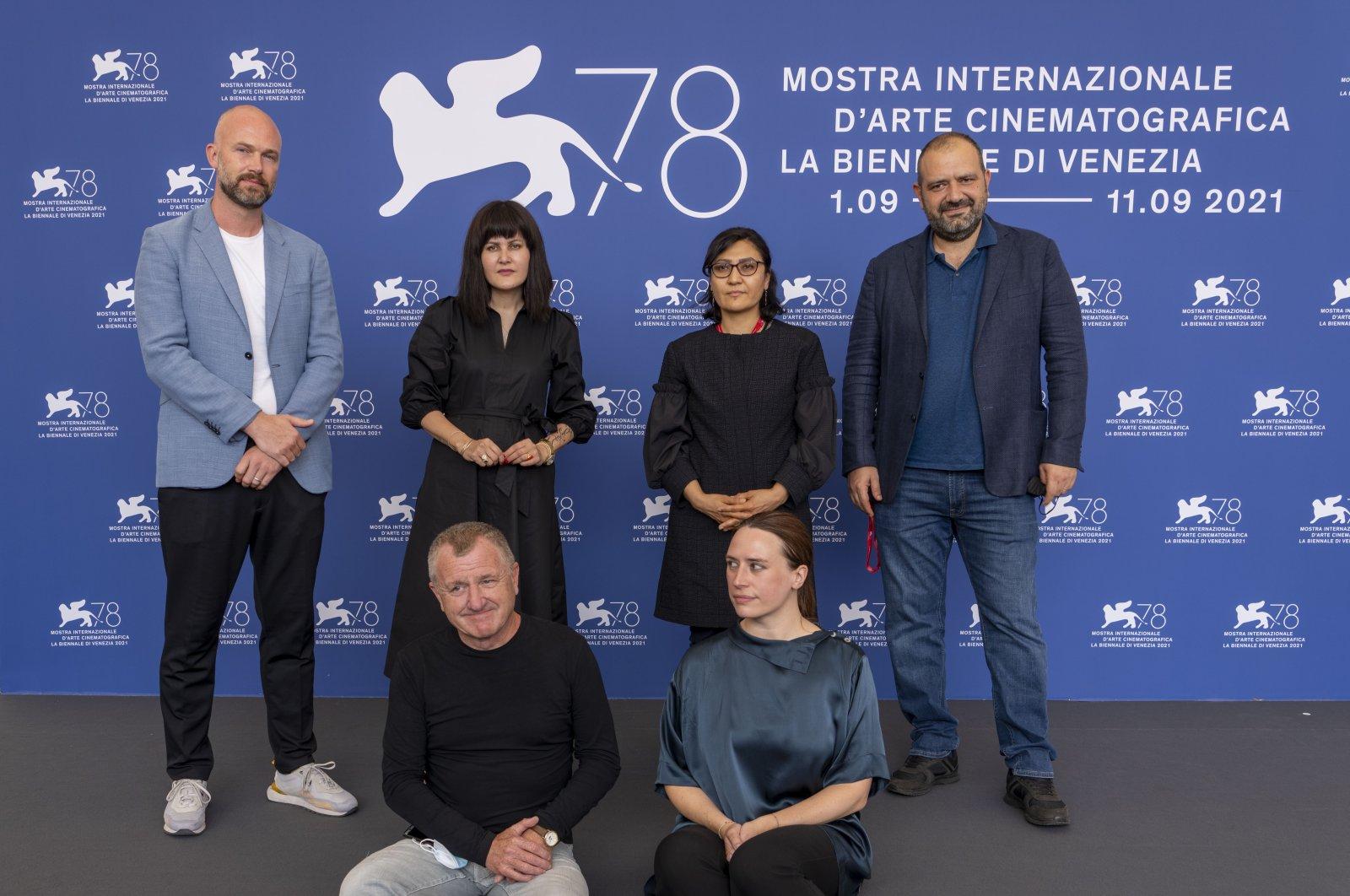 (L-R) Matthijs Wouter Knol, Sahraa Karimi, Sarah Mani, Orwa Nyrabia, Vanja Kaludjercic and Mike Downey pose during the Venice Film Festival, in Venice, Italy, Sept. 4, 2021. (AP Photo)