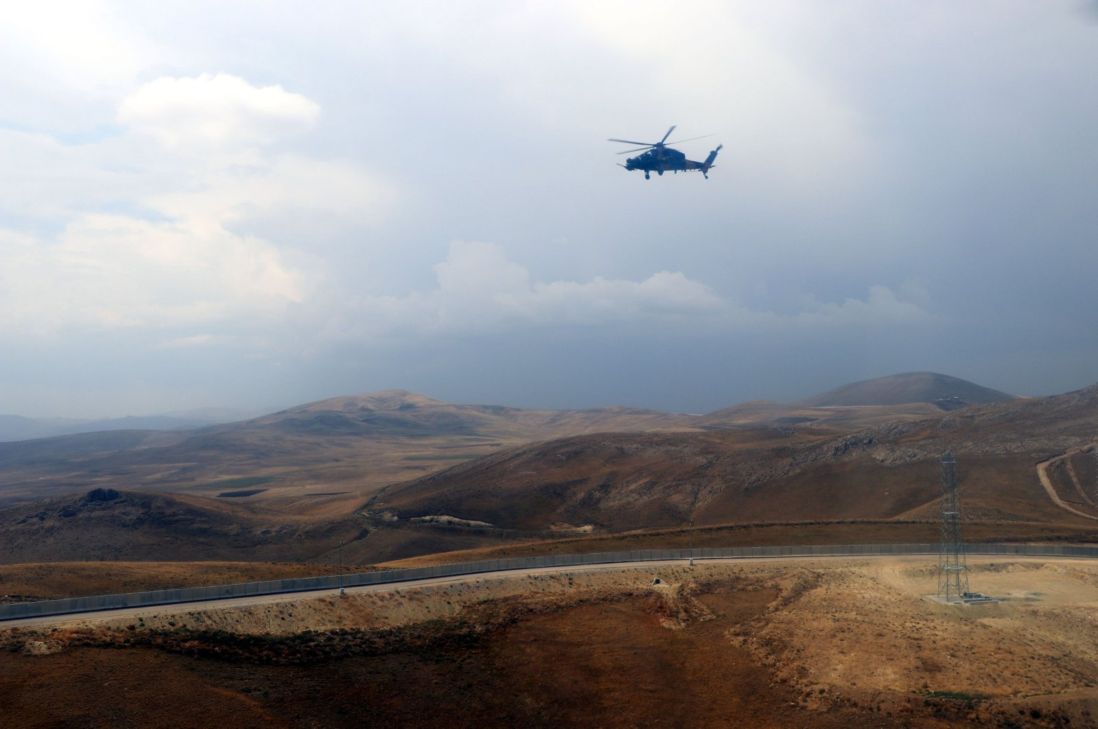 A helicopter flies over the construction of a modular wall across the Turkey-Iran borderline in Van province, eastern Turkey, Aug. 21, 2021. (DHA Photo)