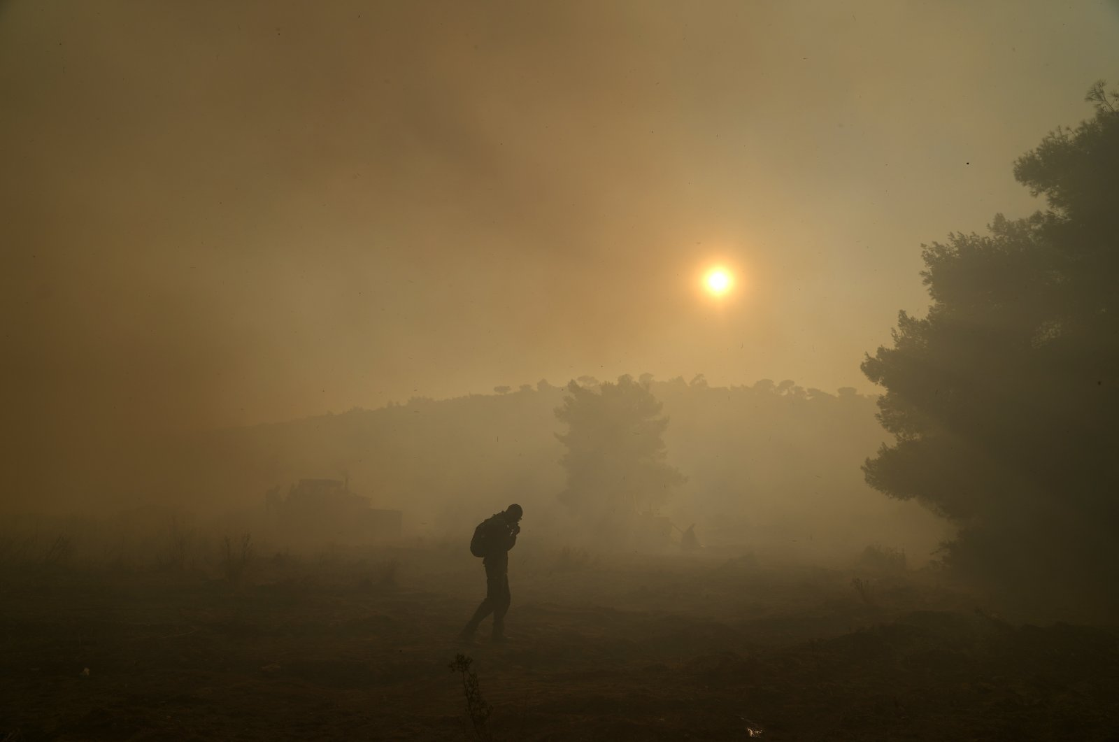 A volunteer works as a bulldozer opens a fire break during a wildfire in Siderina village about 55 kilometers (34 miles) south of Athens, Greece, Aug. 16, 2021. (AP Photo)