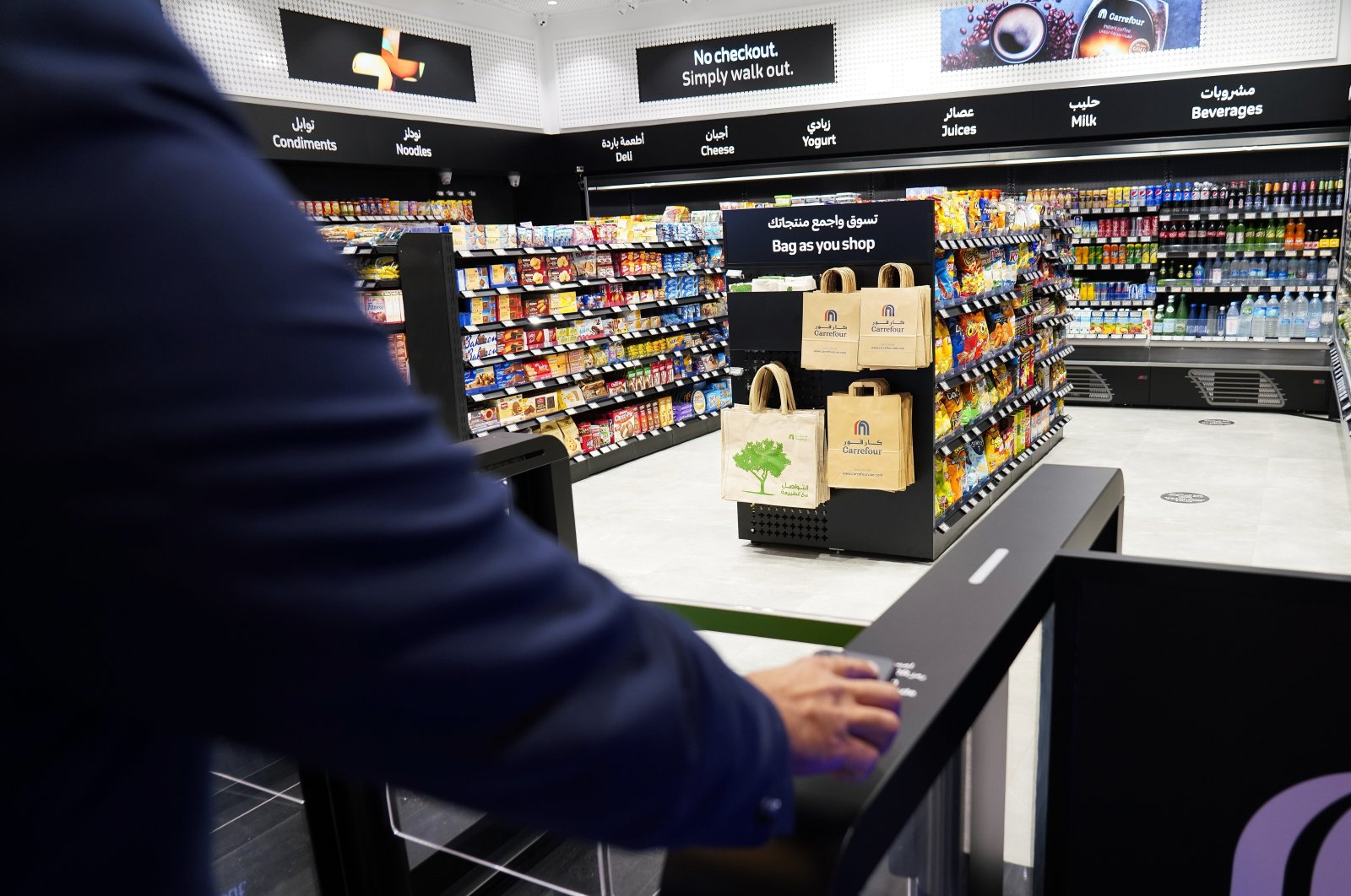 A man uses a QR code on a mobile phone to enter Carrefour's new cashier-less grocery store in Mall of the Emirates in Dubai, United Arab Emirates, Sept. 6, 2021. (AP Photo)