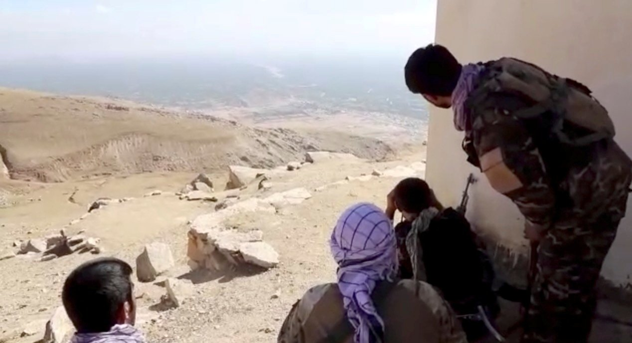 Members of National Resistance Front (NRF) observe by a house near Panjshir Valley, Afghanistan, in this still image obtained from an undated video handout. (National Resistance Front of Afghanistan via Reuters)