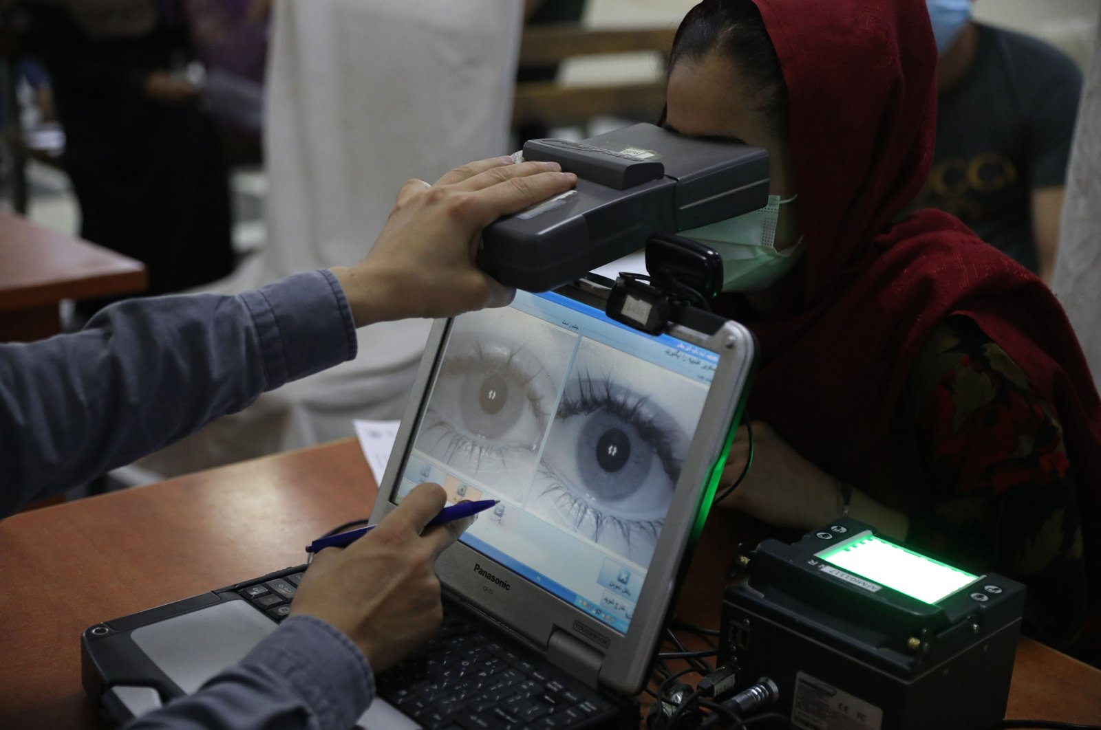 An employee scans the eyes of a woman for biometric data needed to apply for a passport, at the passport office in Kabul, Afghanistan, June 30, 2021. (AP Photo)