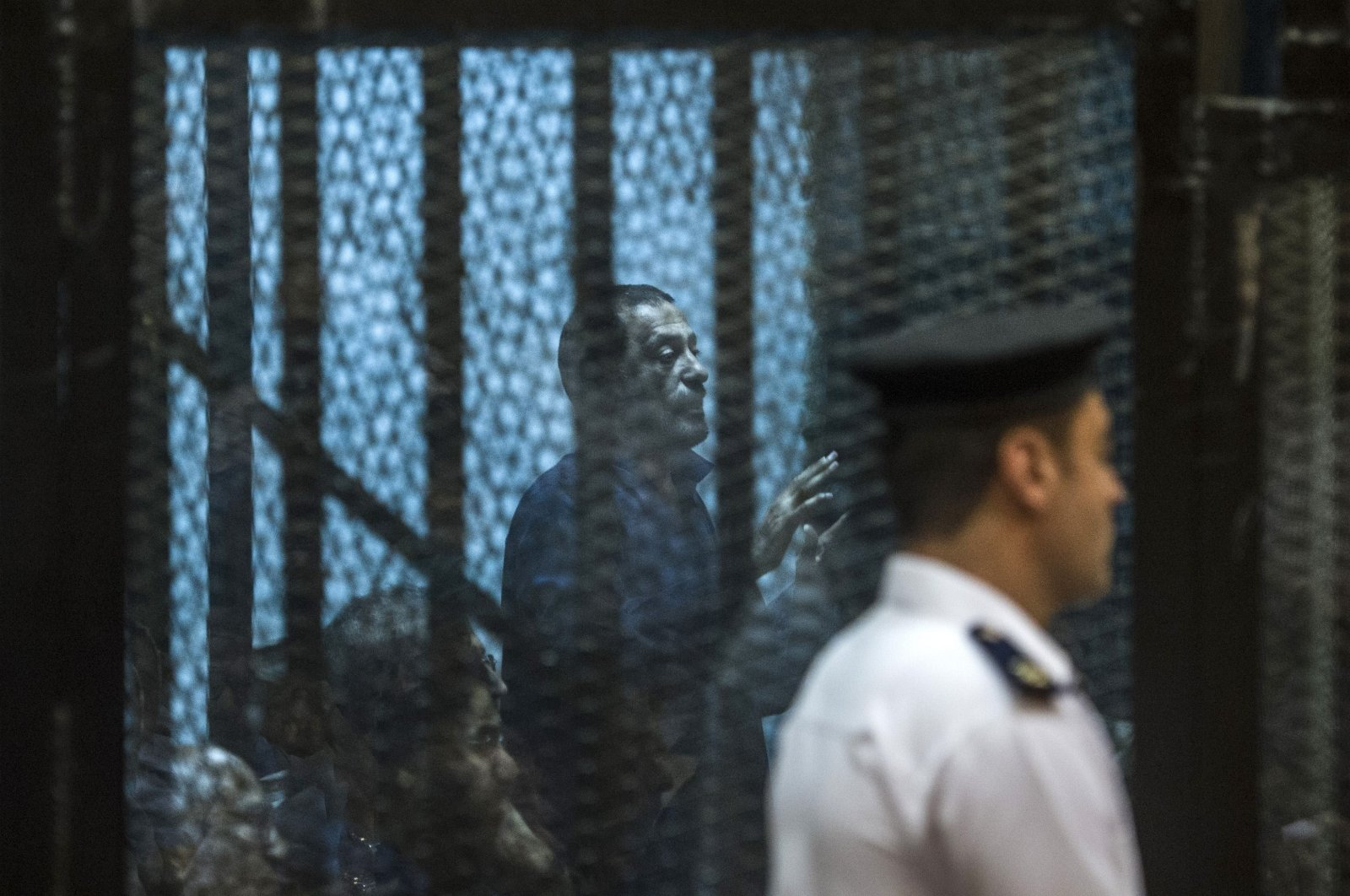 Muslim Brotherhood top figure Ahmed Abou Baraka gestures from behind the defendant's cage during trial for insulting the judiciary alongside 25 other defendants, Cairo, Egypt, May 23, 2015. (AFP Photo)