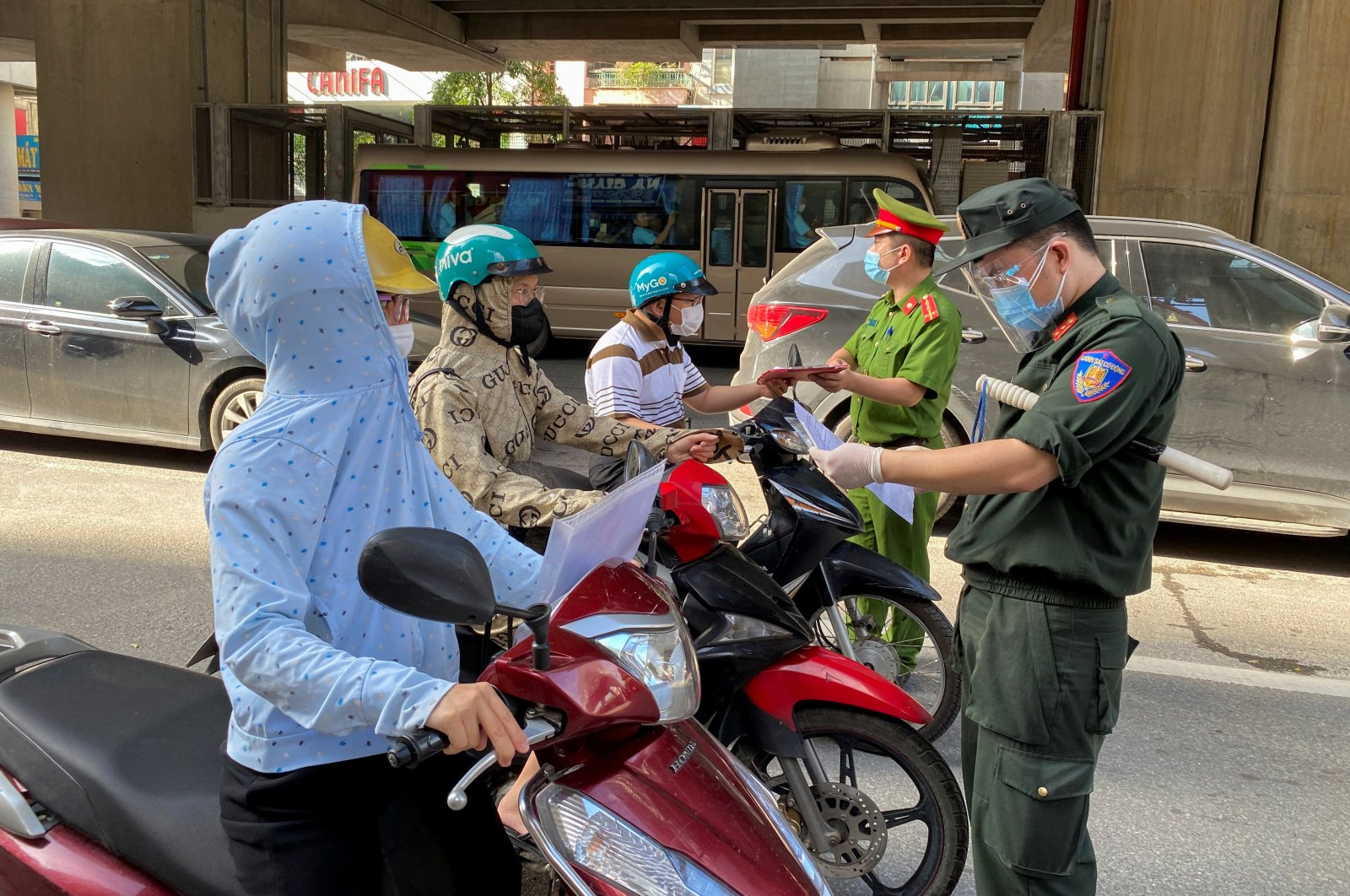 Vietnam police officers inspect authorization travel documents of commuters at a check point during the first day of the extended lockdown in Hanoi, Vietnam, Sept. 6, 2021. (Reuters Photo)