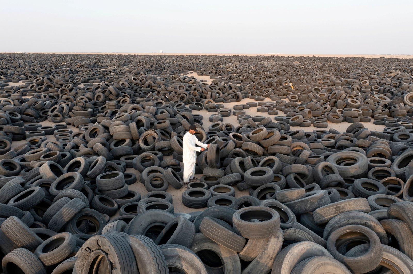 A contractor stands among used tires destined for recycling in Salmi, Kuwait, Sept. 4, 2021. (Reuters Photo)