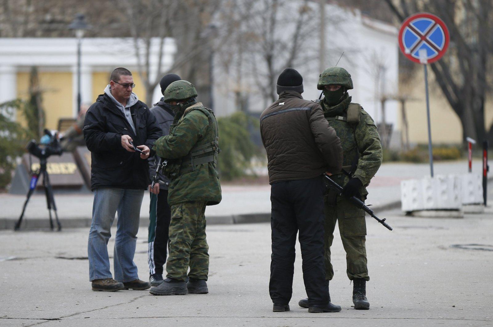 Armed men check journalists' documents around the regional parliament building in Simferopol, Crimea, occupied Ukraine, March 1, 2014. (Reuters Photo)