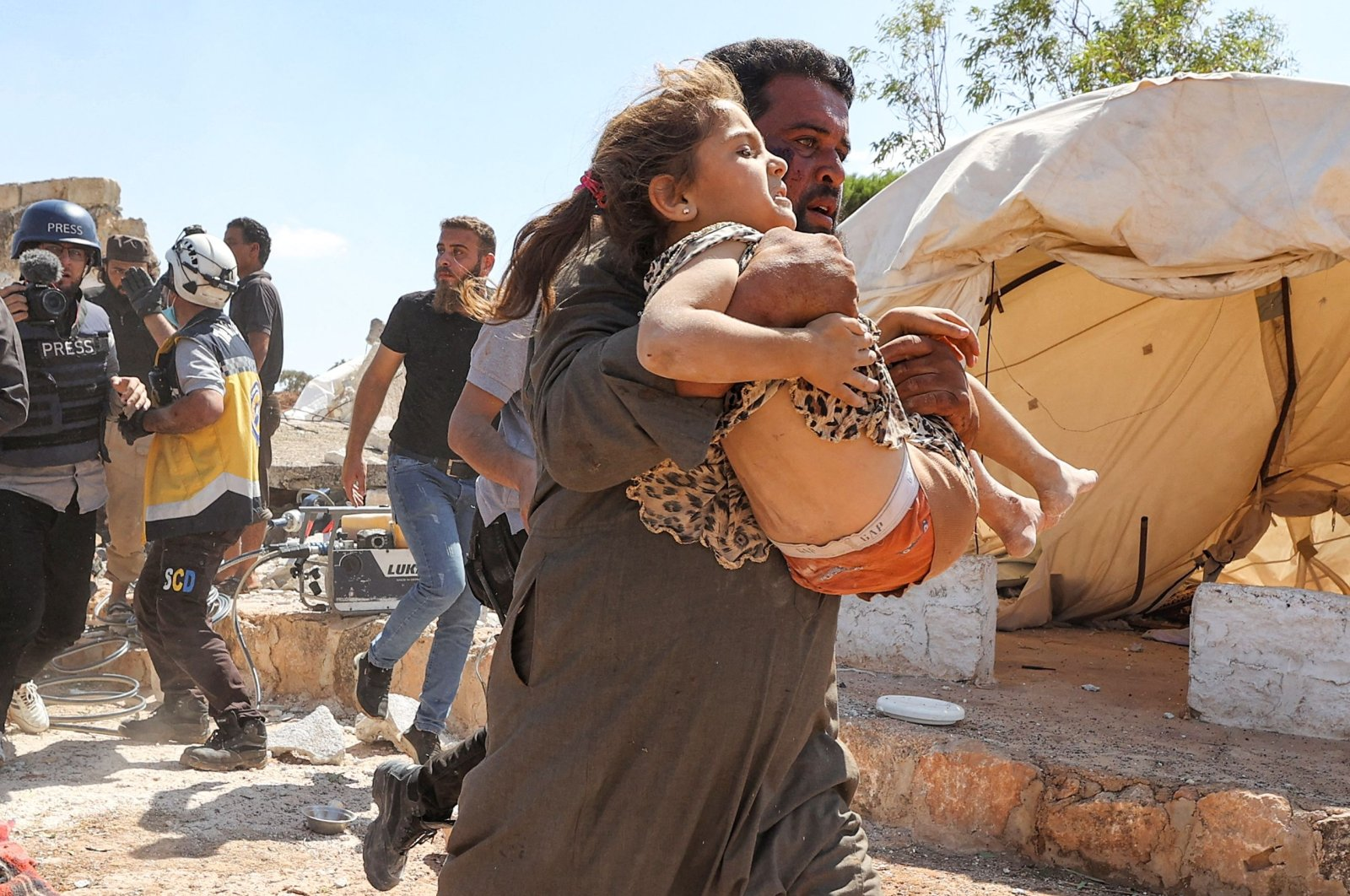 A man carries away a girl that was injured during aerial bombardment near a make-shift camp for displaced Syrians near the town of Kafraya in the north of Syria's Idlib province, Sept. 7, 2021. (AFP Photo)